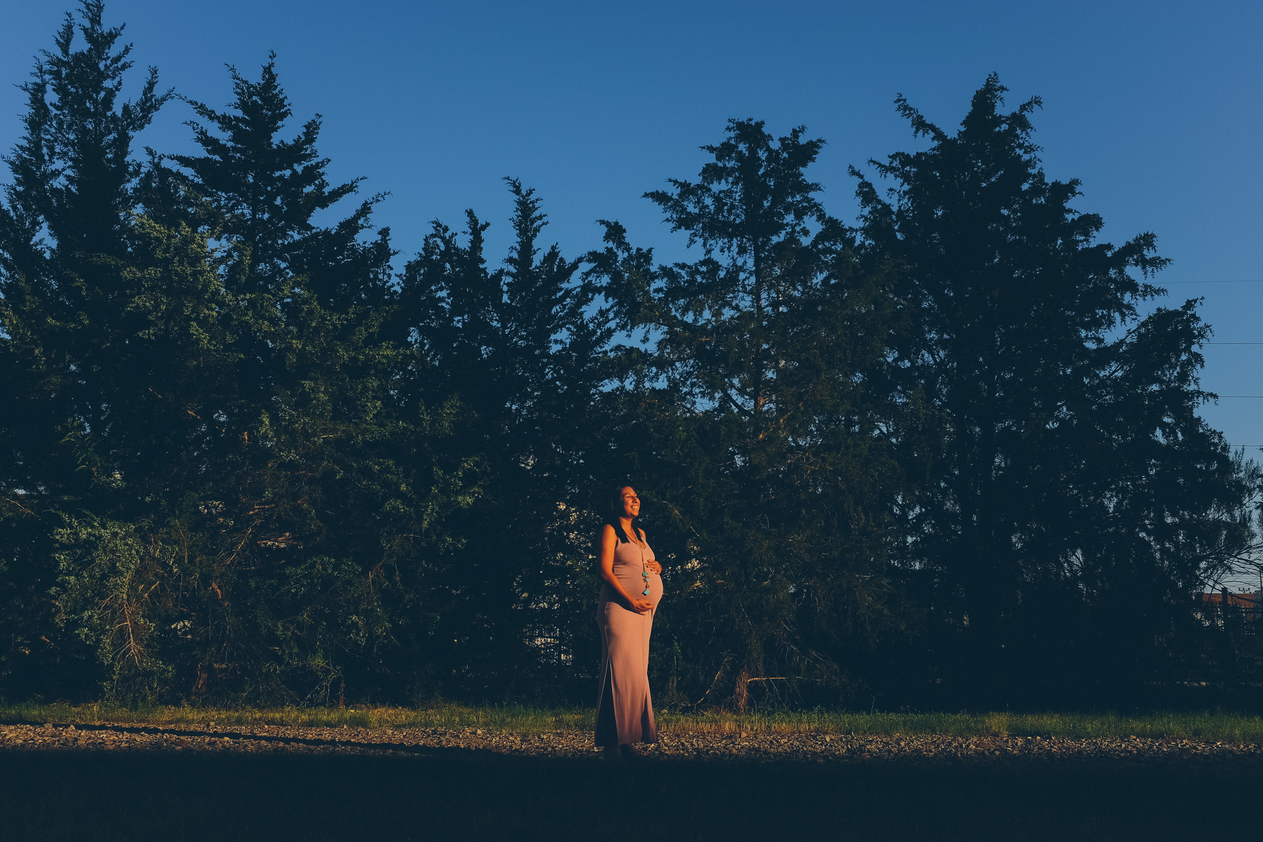 Photograph of pregnant woman in front of grove of trees