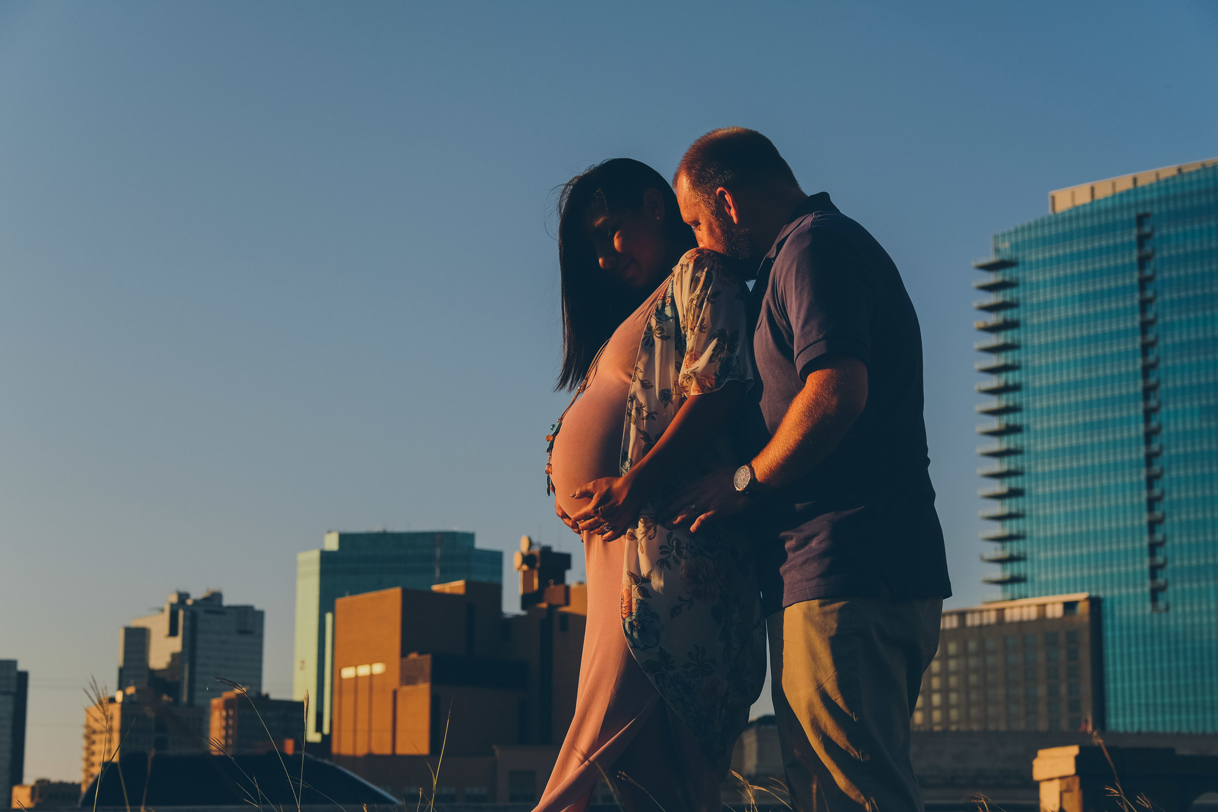 Couple hugging while holding womans pregnant belly with city skyline in background