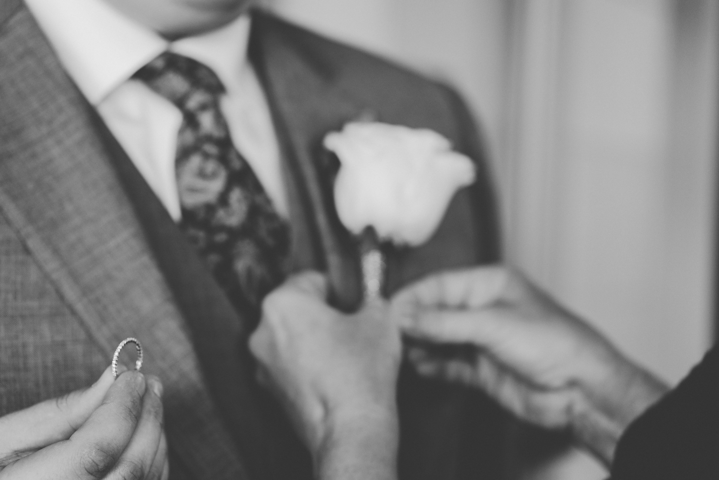 Groom holding wedding ring while getting dressed