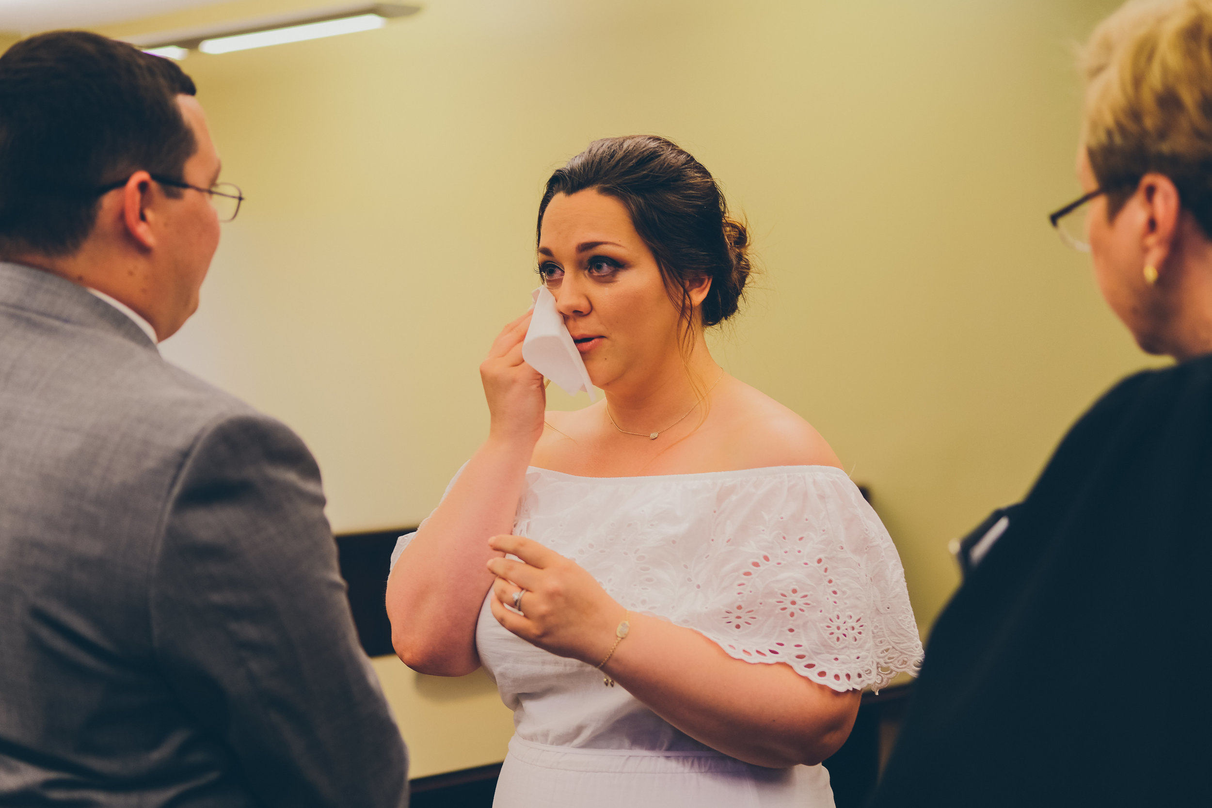 Photo of bride wiping away tears during ceremony