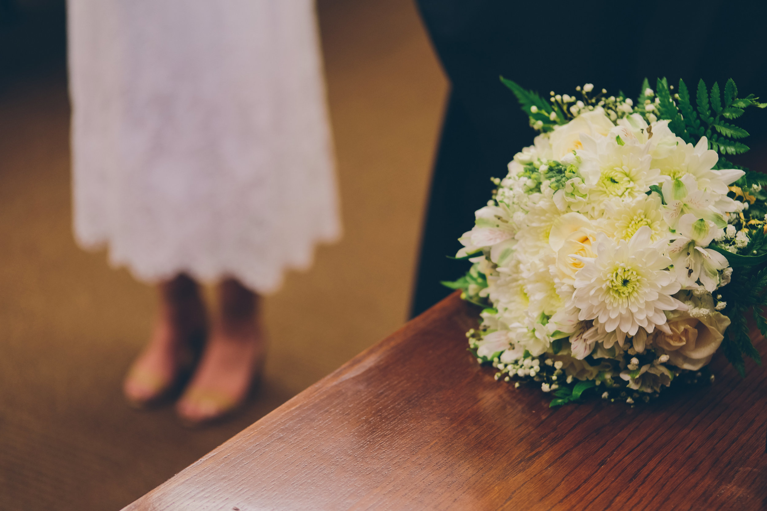 Wedding flowers in foreground and grooms feet in background.