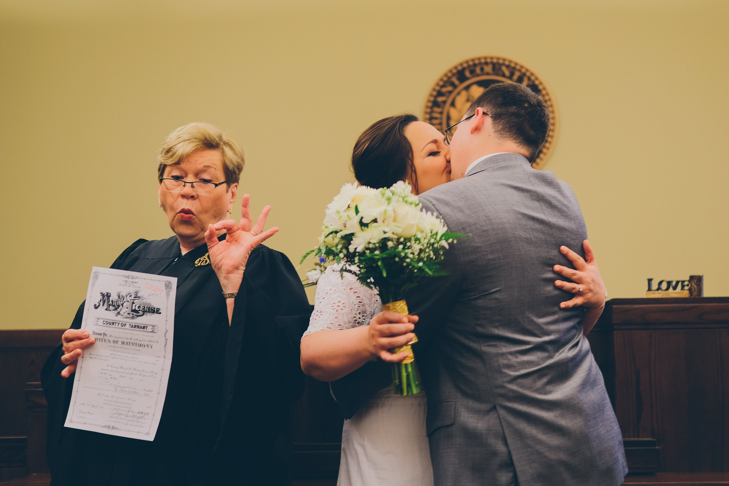 Bride and groom kissing and judge giving thumbs up