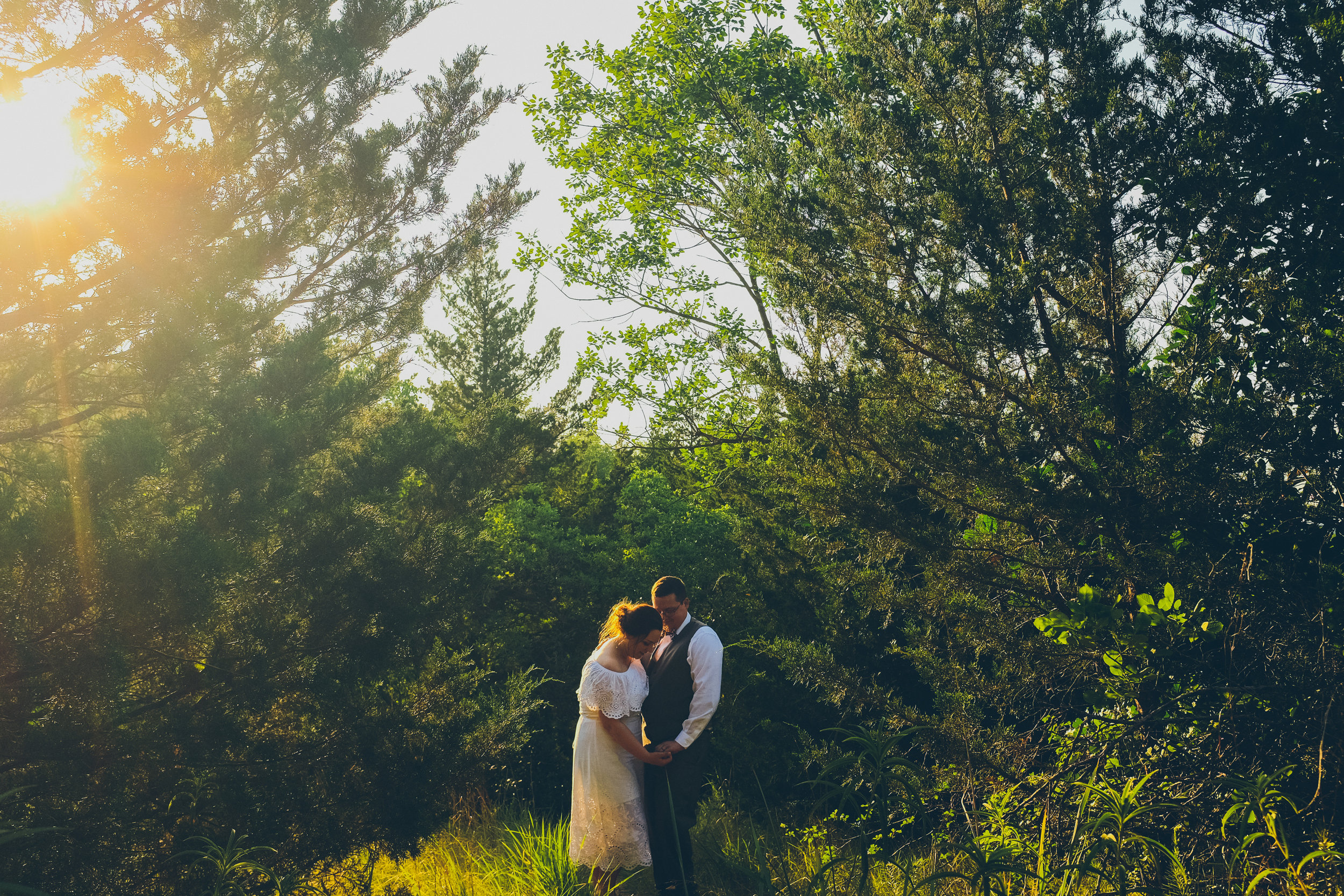 Bride and groom standing in the woods with sun off to the side