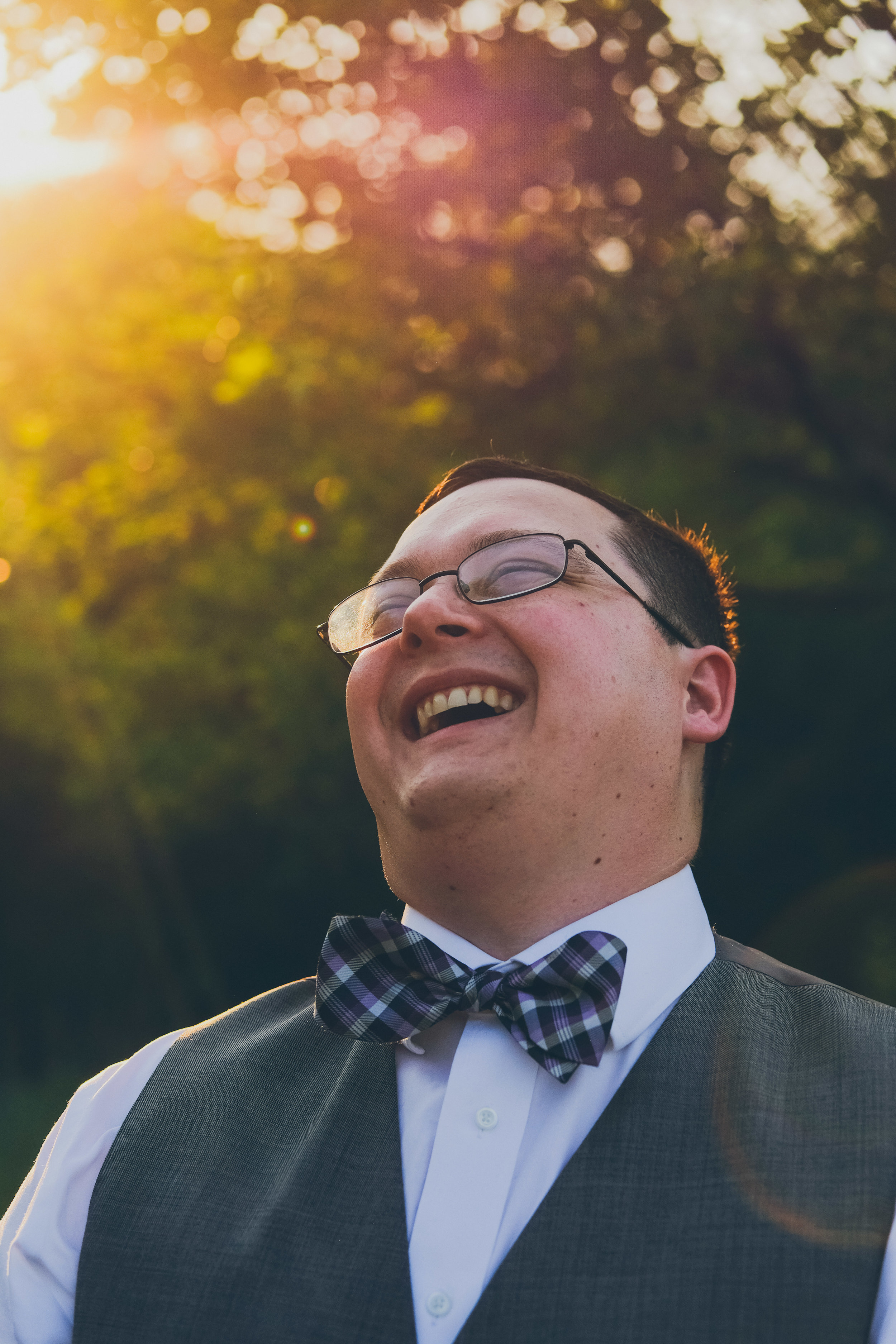 Groom laughing and wearing bowtie with sun over shoulder