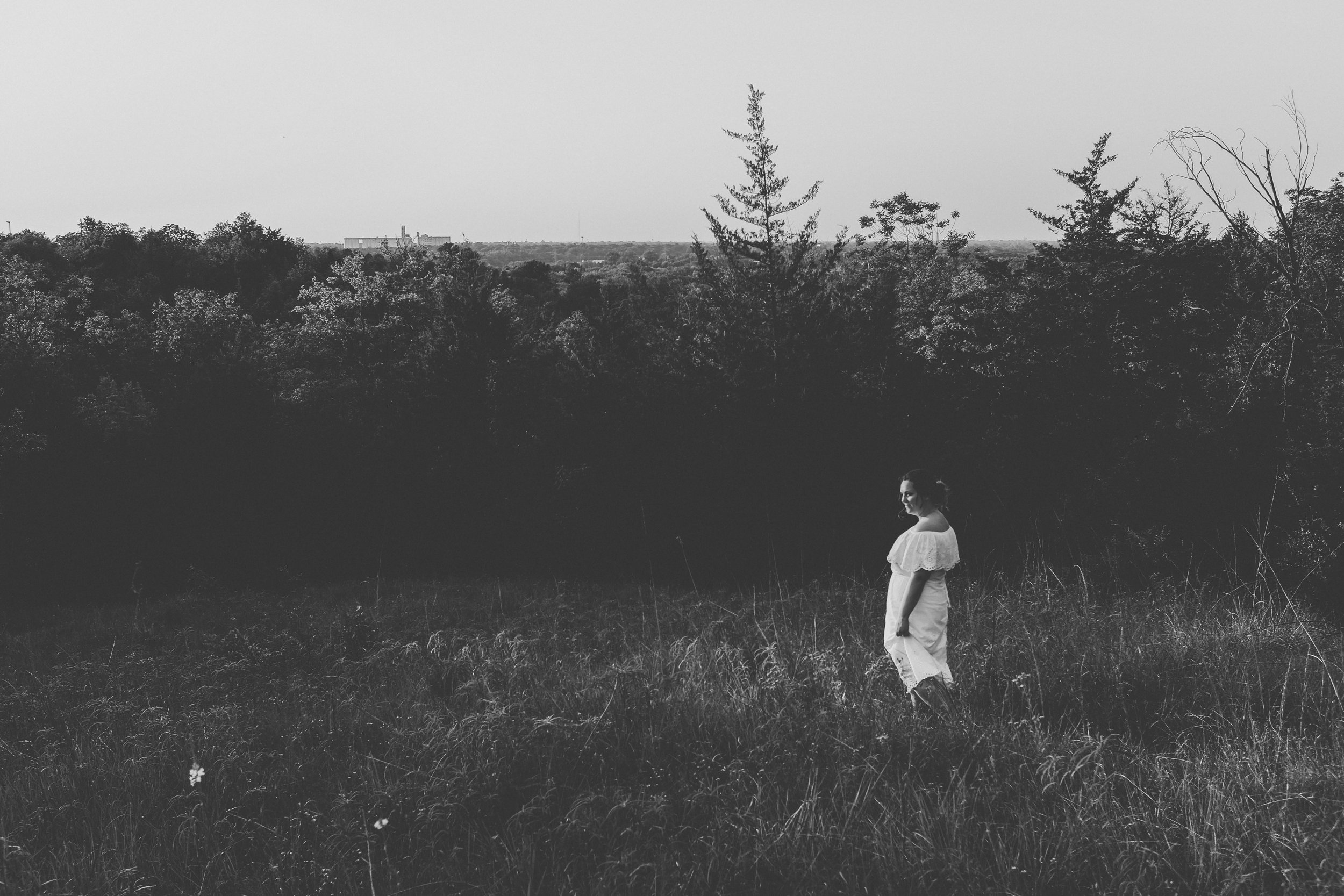 Black and white photo of bride in wedding dress walking in the woods