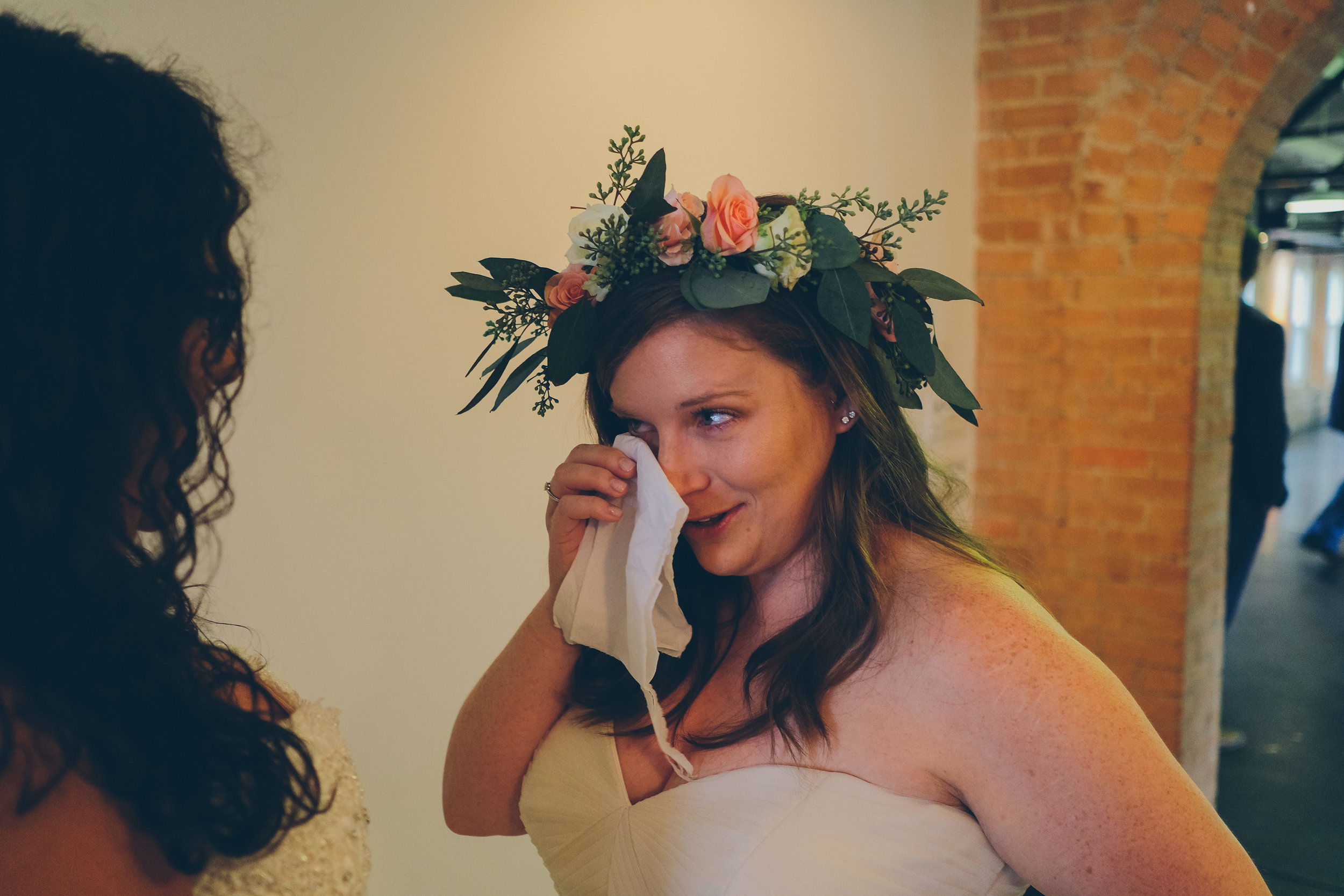 Color photo of bride wiping tears from her face.