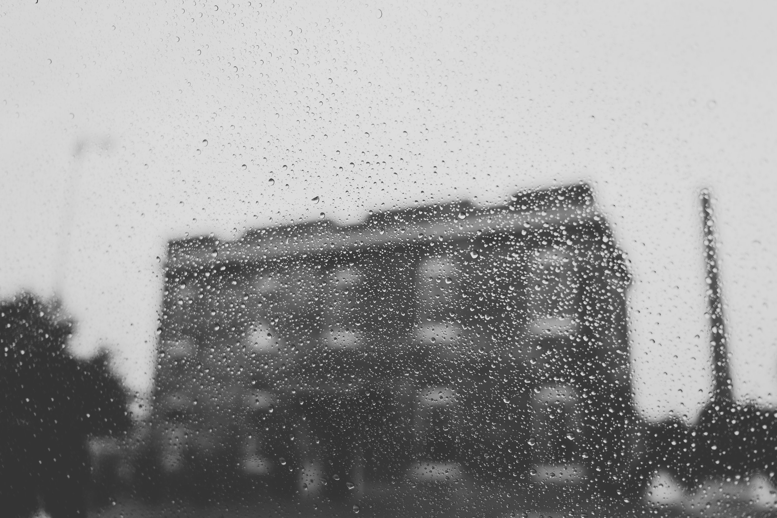 Photograph of rain drops on a window with The Filter Building in background.