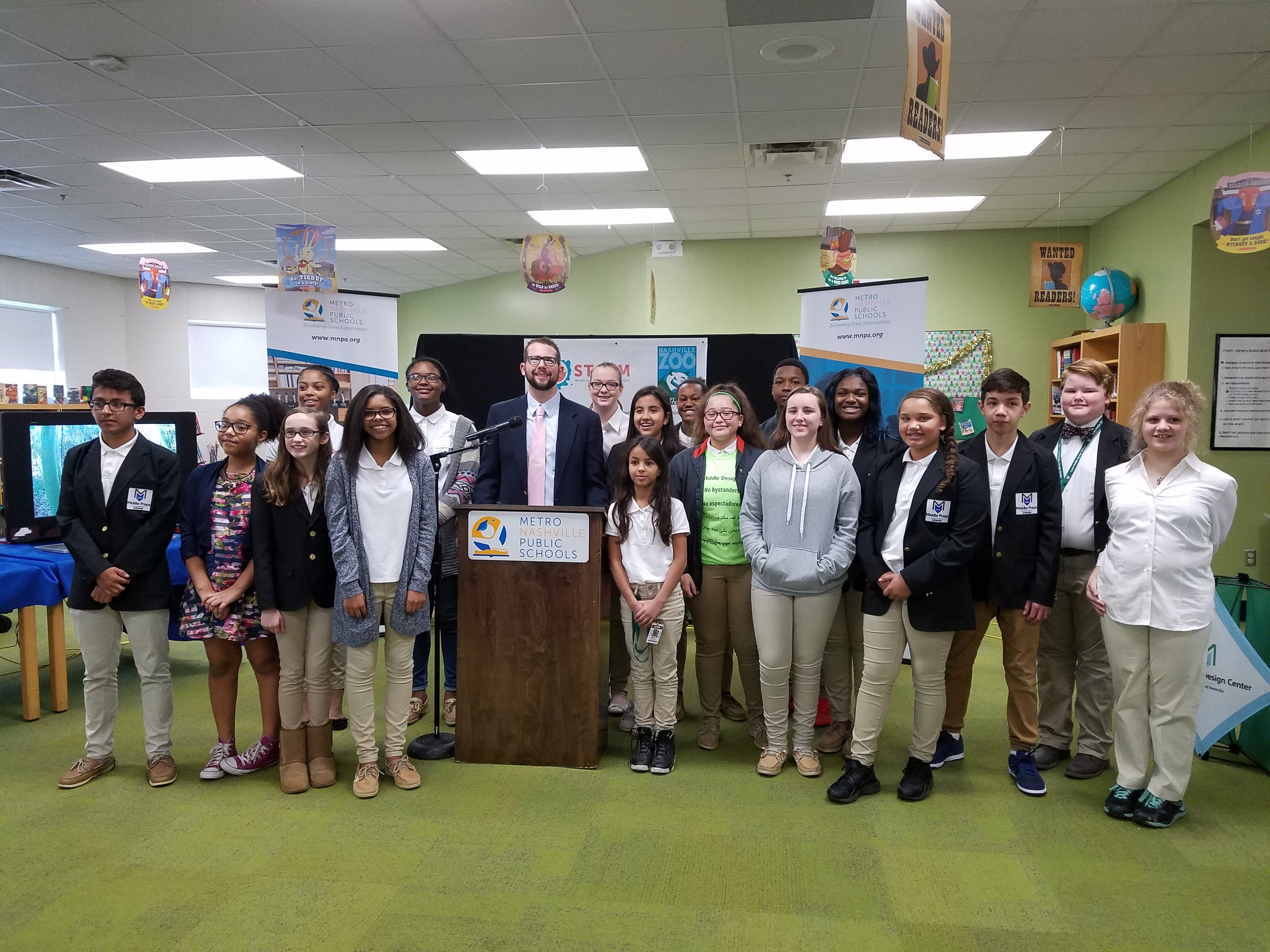Principal Dr. Jeremy Lewis stands with 6th, 7th and 8th grade students working with the new zoo technology.