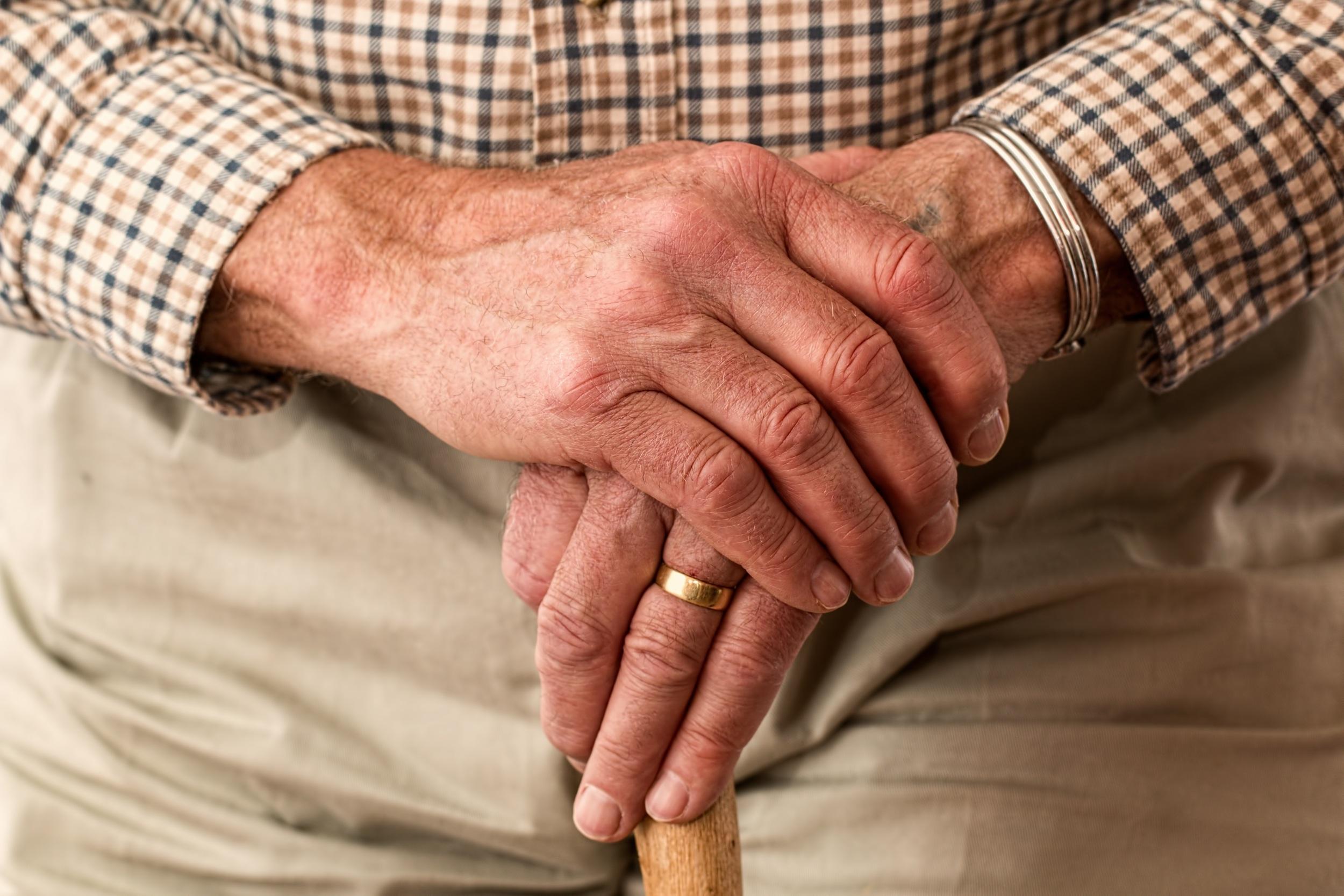 Hands of older man holding a cane