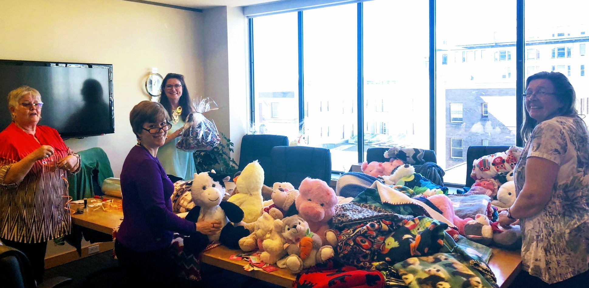 Staff help wrap stuffed animals in the McBOP board room