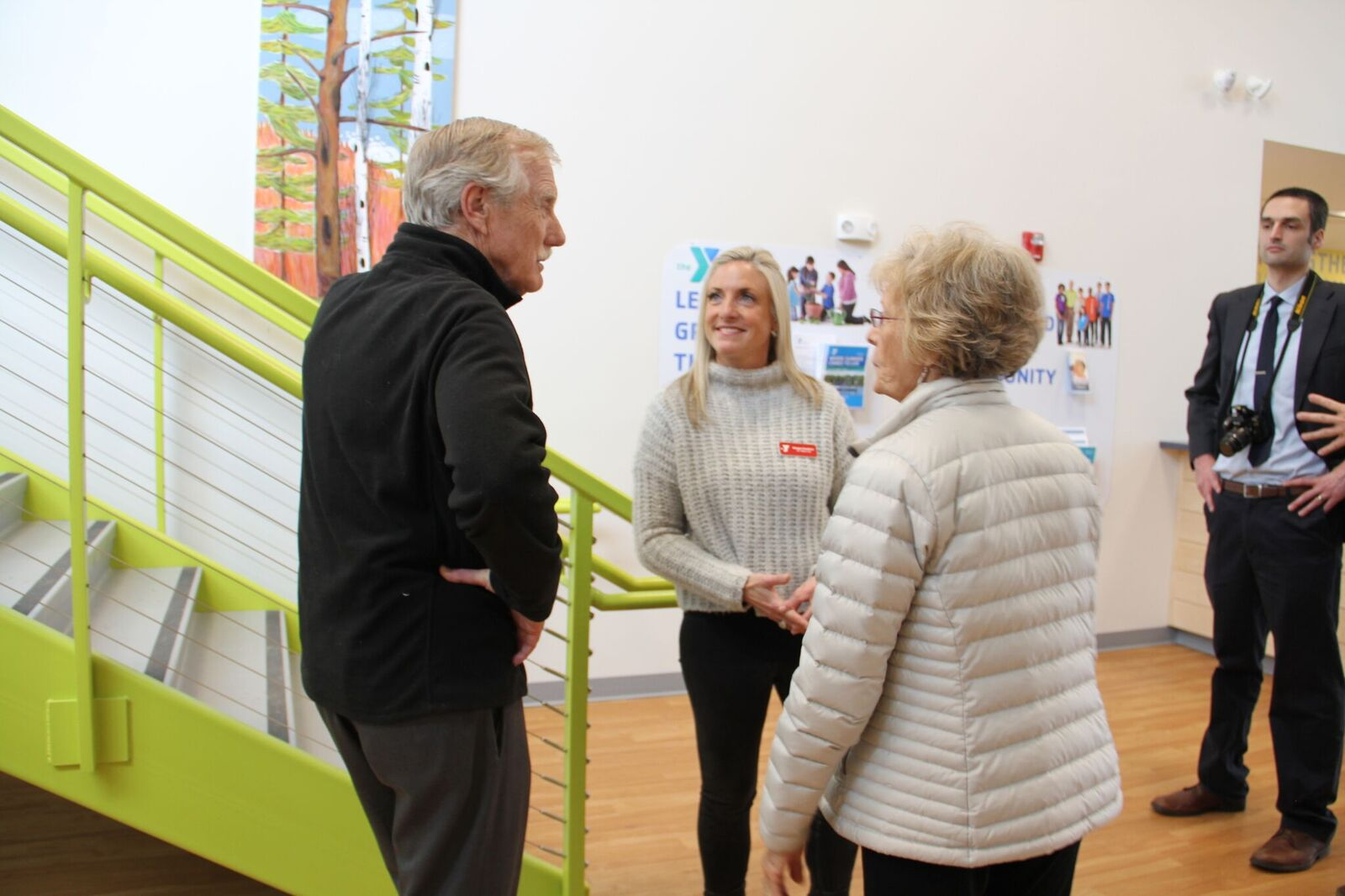 Senator Angus King of Maine, the YMCA's CEO Meagan Hamblett and a local artist.