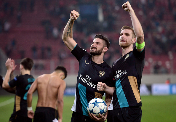 Arsenal's French forward Olivier Giroud (L)and Arsenal's German defender Per Mertesacker celebrate after the UEFA Champions League Group F football match between Olympiacos and Arsenal. (Photo by LOUISA GOULIAMAKI/AFP/Getty Images)