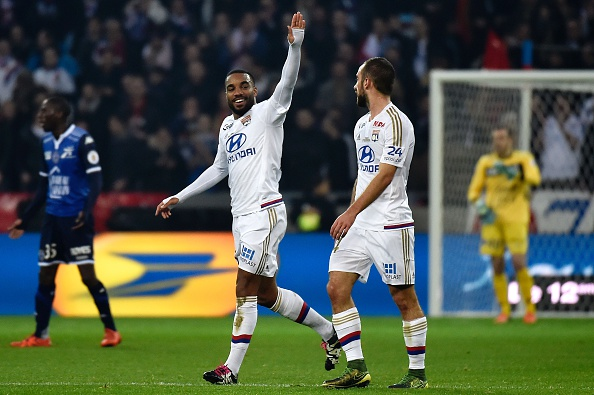 Lyon's French forward Alexandre Lacazette (c) celebrates with teammates after scoring a goal during the French L1 football match between Olympique Lyonnais (OL) and Troyes on January 9, 2016, at the New Stadium in Decines-Charpieu, centraleastern France. AFP PHOTO / JEFF PACHOUD / AFP / JEFF PACHOUD (Photo credit should read JEFF PACHOUD/AFP/Getty Images)