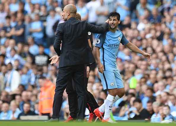 Guardiola gives a pat to Nolito after the latter lost his cool in the 86th minute of City's game against Bournemouth and earned himself a red card. (Photo by Paul Ellis/AFP/Getty Images)