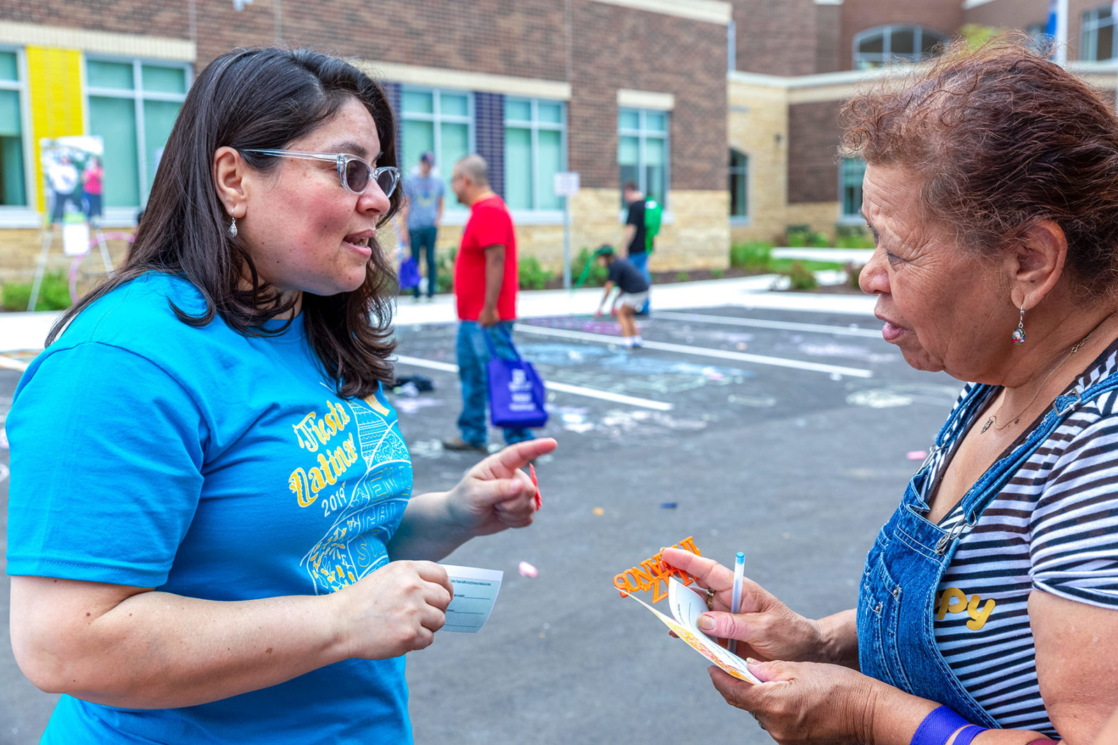 Marylu Ramirez (L) chats with a community member at the Fiesta Latina at Comunidades Latinas Unidas en Servicio (CLUES) in St. Paul's East Side on Aug. 10, 2019. Photo courtesy Kerem Yucel for MPR News