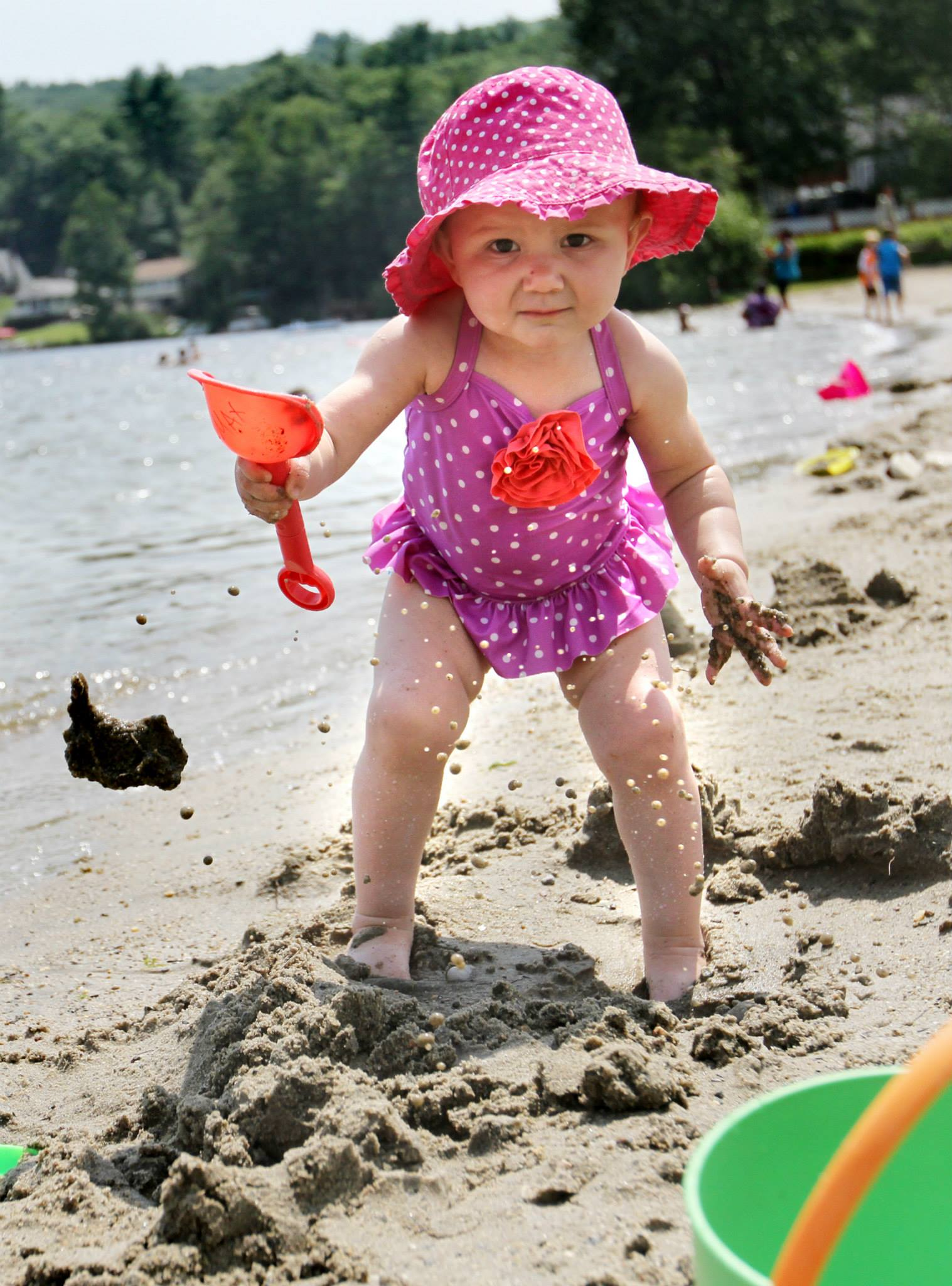 SHUTESBURY, MASS. -- Madison Suchecki, 17 months, of Belchertown flings sand into the air while visiting Lake Wyola in Shutesbury on Tuesday. (Recorder/Micky Bedell)