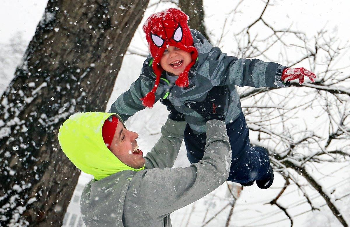 GREENFIELD, MASS. -- Tim Caplice lifts Carter Malouin, 3, into the air while enjoying the first fresh snow of the season in Greenfield on Wednesday. (Recorder/Micky Bedell)