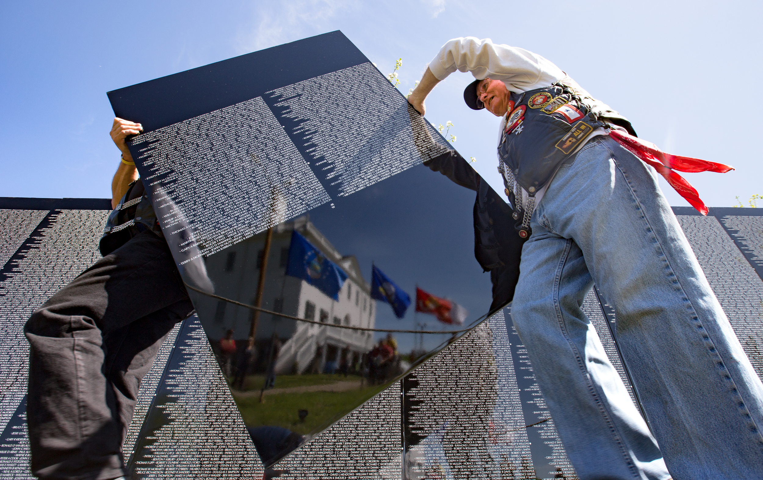 """THOMASTON, MAINE -- 05/26/2016 -- Roland Scott Jr. (right), of Westbrook, also known as """"Atom Ant"""" by other riders in the Combat Veterans Motorcycle Association, helps fellow rider and veteran Terry L. Wright Sr., """"Starlifter"""", of Gorham, carry a piece of The Moving Wall at the Knox Museum on Thursday during the wall's installation. Since 1984 the half-size replica of the Vietnam Veterans Memorial has been traveling the U.S.(Micky Bedell   BDN)"""