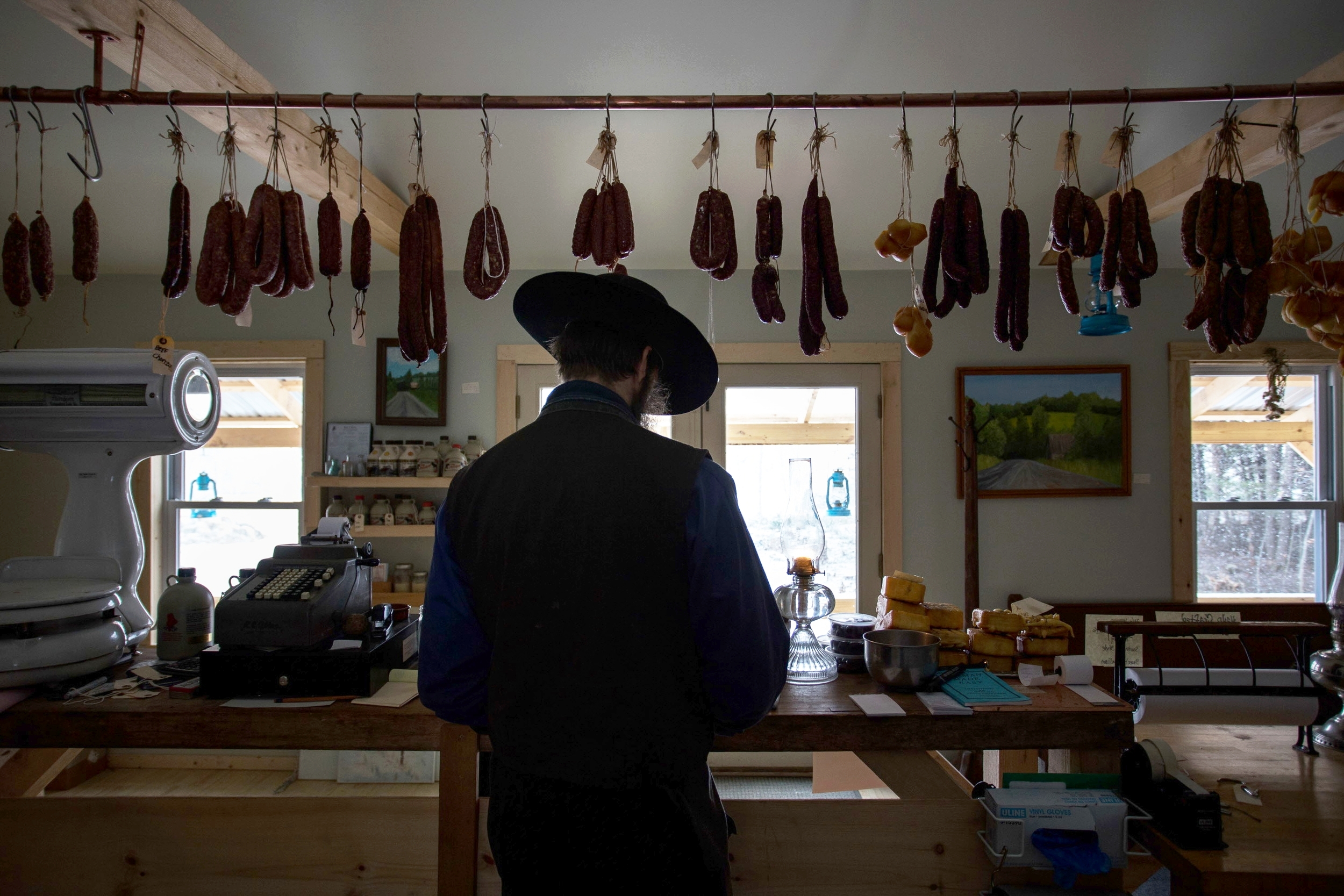 """UNITY, MAINE -- 01/12/2016 --Matthew Secich, 45, owns and manages an artisanal charcuterie as part of the thriving Amish community in Unity.Everything in the store is crafted sans electricity and other modern comforts, at prices """"anyone can afford,"""" he said.Secich and his family became Amish a few months ago. They moved to Unity, which has a thriving Amish community, and forsook many aspects of the modern world, including electricity. Secich has traded in his five cars for three horses, bright lights for the softer glow of lanterns and his white chef coat for drab Amish clothes and an impressive beard. (Micky Bedell   BDN)"""