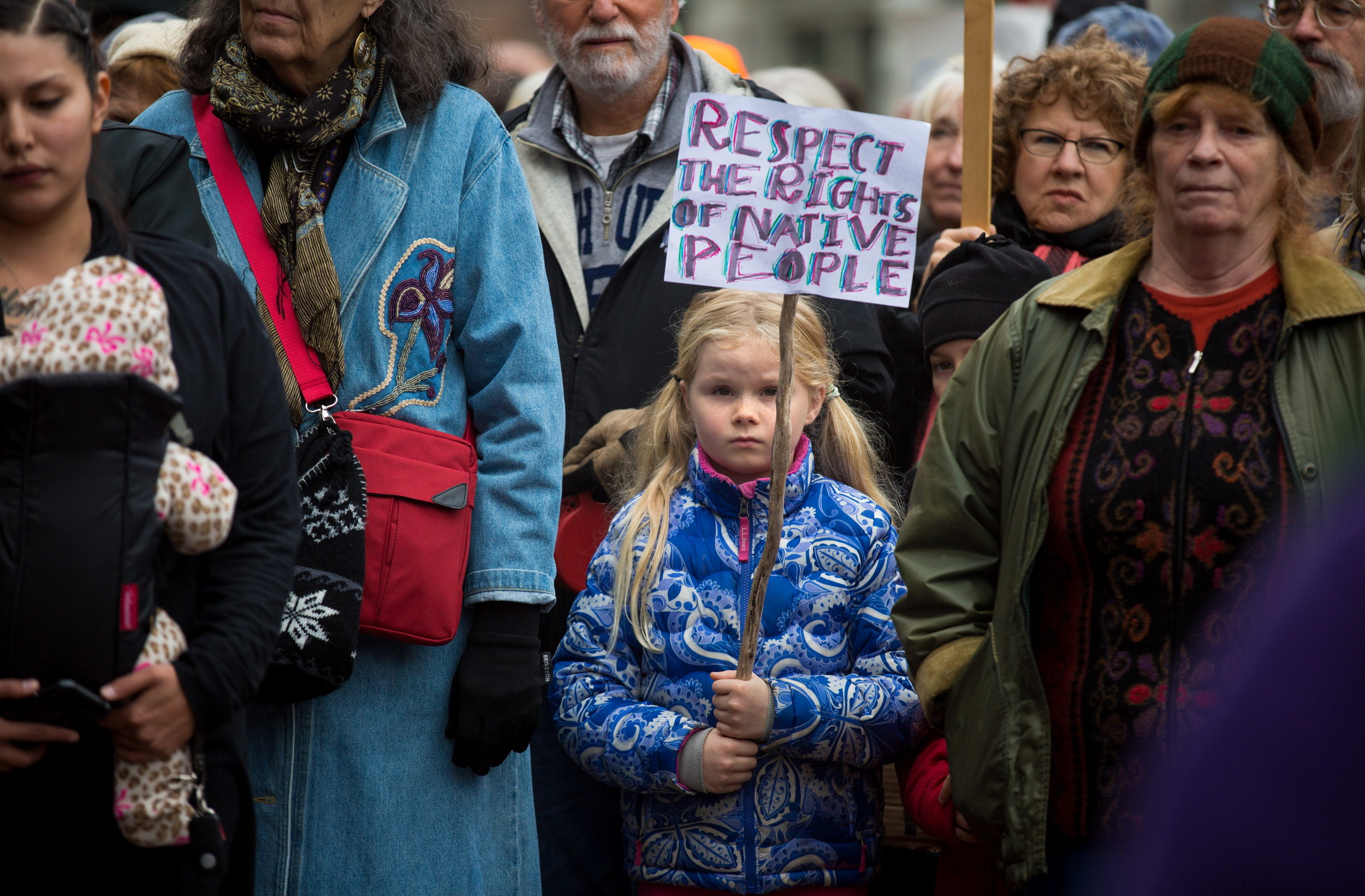 """BANGOR, MAINE -- 11/15/16 -- Eva Beal, 8, of Ellsworth holds a sign she made herself during a Dakota Access Pipeline protest in West Market Square in Bangor on Tuesday afternoon. Over 100 protestors gathered as part of a national day of action to call for the permanent rejection of the Dakota Access Pipeline, currently under """"the threat of the Trump presidency,"""" and to stop violence against protestors by a """"militarized police,"""" according to protest organizers. The event spanned all 50 states and included thousands of protestors and dozens of social justice and environmental groups. (Micky Bedell   BDN)"""