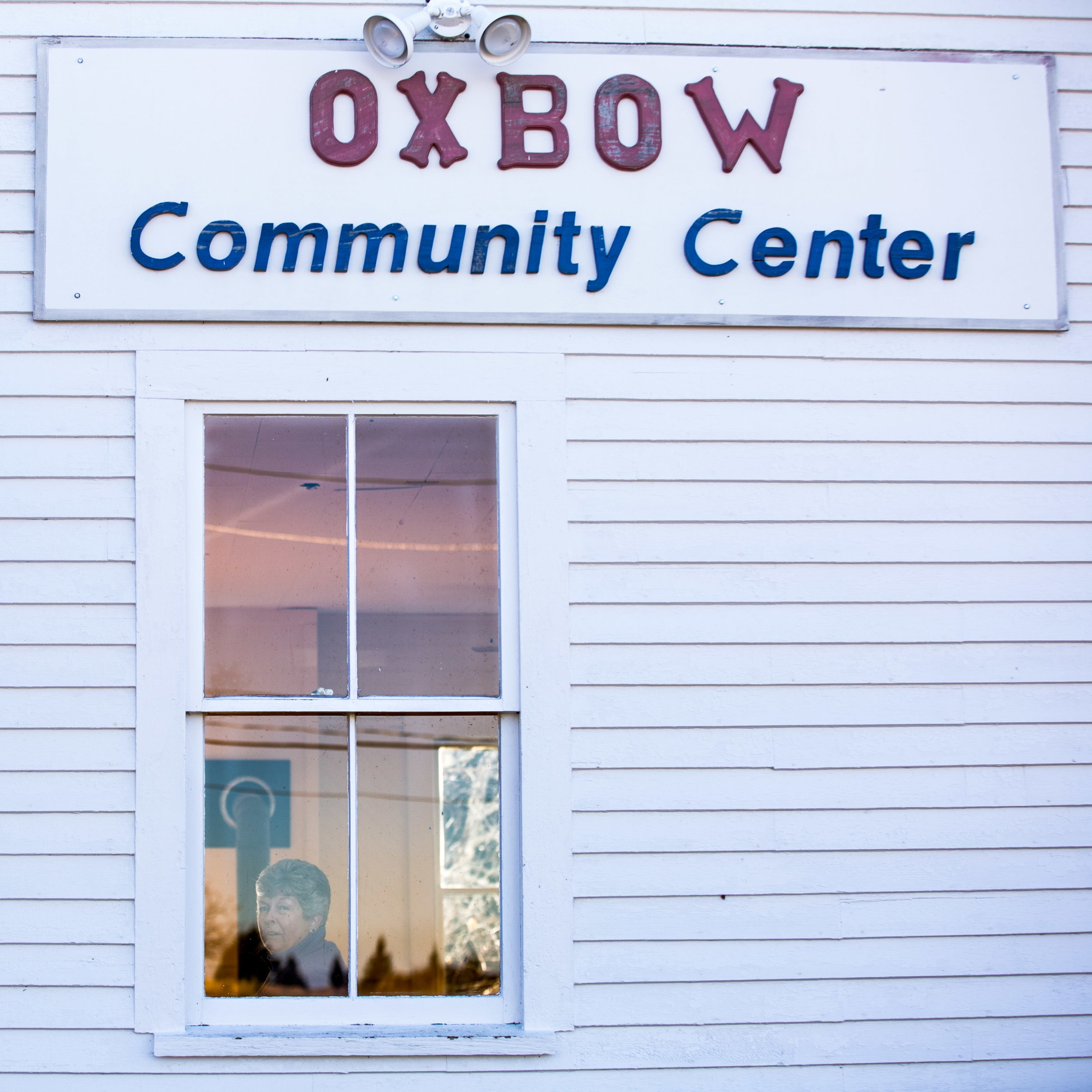 OXBOW, MAINE -- 11/08/2016 --Judy Gray peers out the front window of the Oxbow Community Center on election day, as the town votes for deorganization after years of petitioning and paperwork. The transition to a service economy has changed Maine's most rural towns. To preserve their sense of place, individual communities face a choice about their future: Accept a fate of likely continued decline, or adapt with no guarantee their efforts will work. (Micky Bedell   BDN)