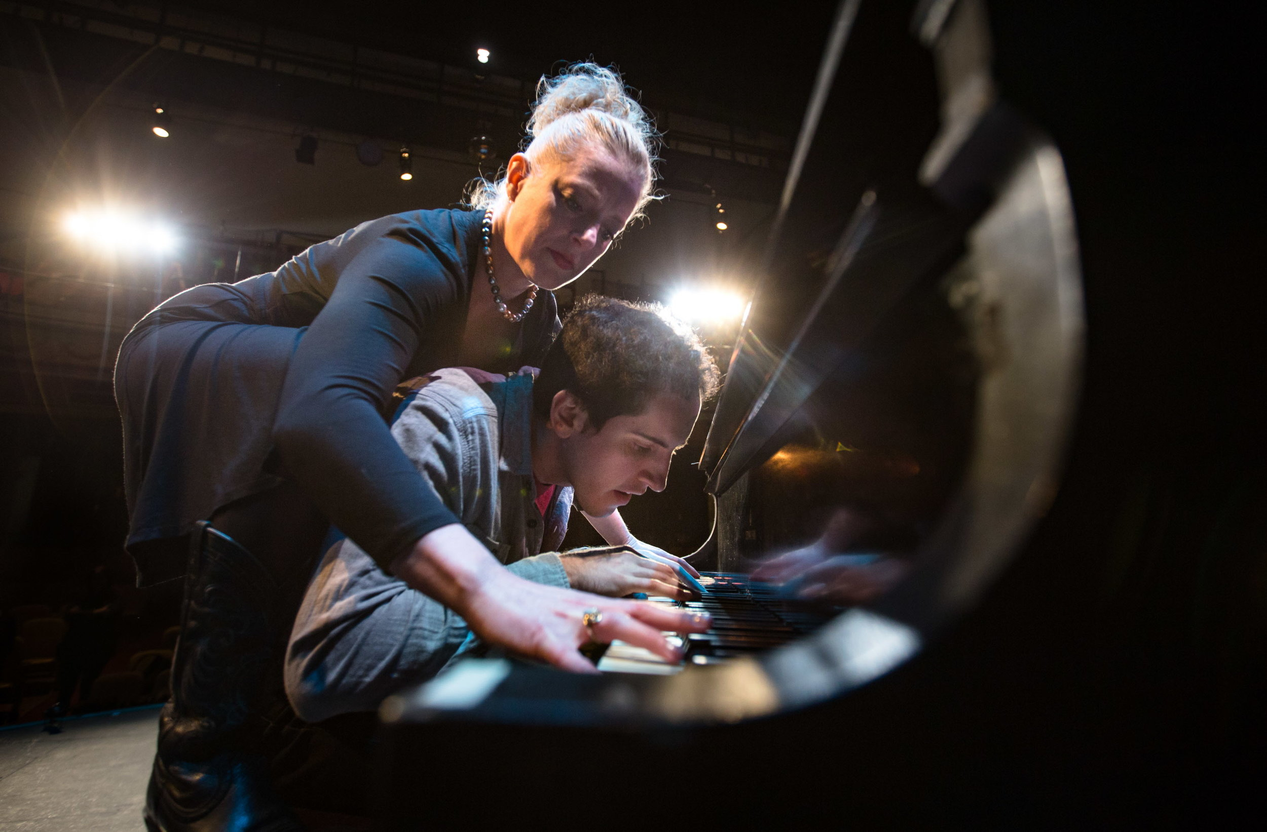 """BANGOR, MAINE -- 10/14/2016 -- Danielle Erin Rhodes reaches over Jason Cohen to play a duet on the piano at Penobscot Theatre Company in Bangor while practicing for their show """"Murder For Two,"""" opening Oct. 21. The premise of the upcoming production of new musical """"Murder For Two"""" is pretty simple: Small-town cop Marcus Moscowitz (played by Cohen) tries to figure out which of 12 suspects killed novelist Arthur Whitney. It's a murder mystery; perfect Halloween-season fun. Of course, there's a twist. All 12 suspects are played by actor Danielle Erin Rhodes — and there's only two actors for the whole production. There's also no band. Both Cohen and Rhodes play the piano — sometimes both at the same time — the only musical accompaniment in the show. They're also their own music directors. They dance, too. Plus there's countless super-fast costume changes. (Micky Bedell   BDN)"""