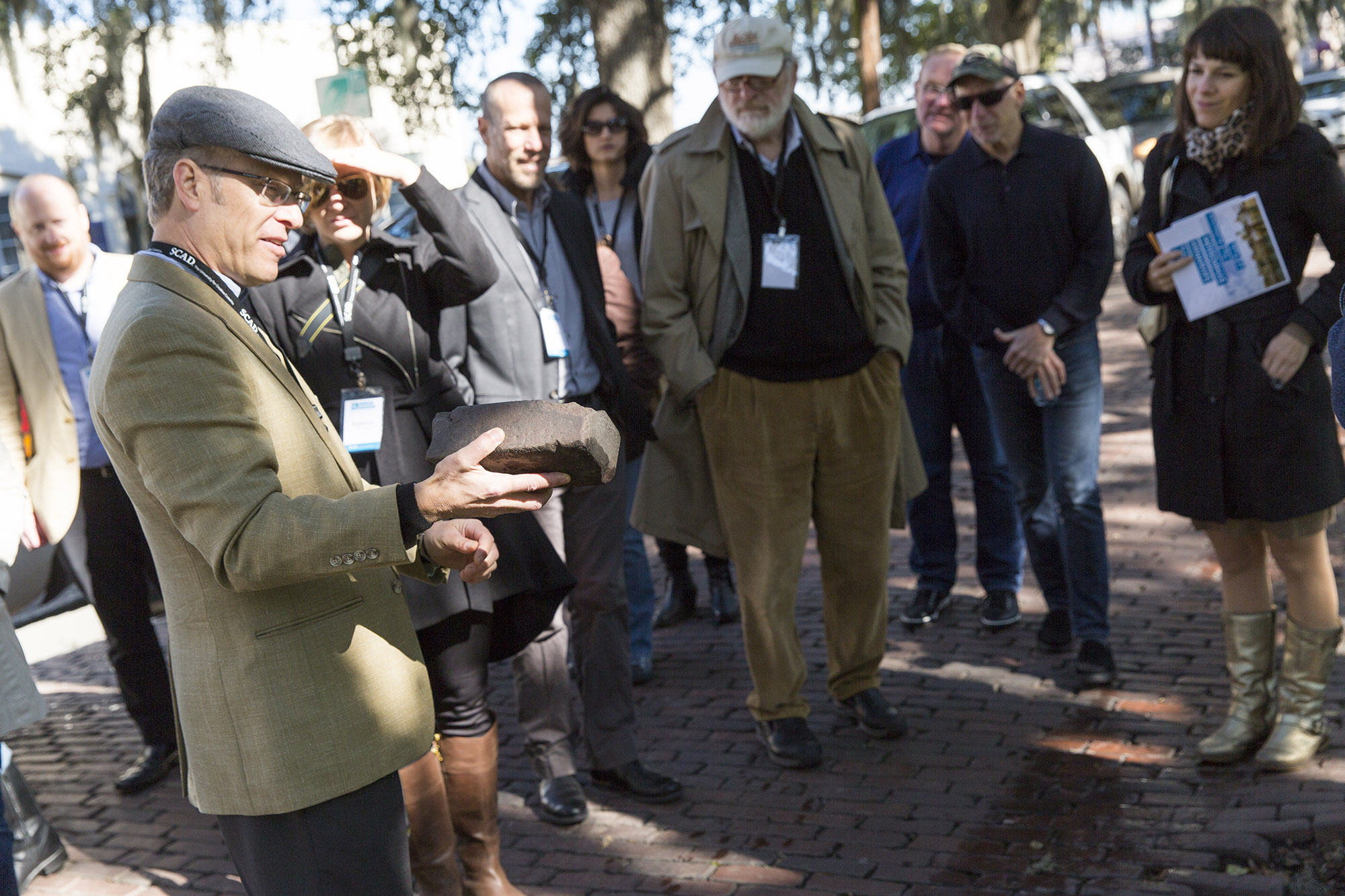 Site author Robin B. Williams leading a walking tour during the 9th Savannah Symposium: The Architecture of Trade, pointing out that the vitrified bricks used to pave Rossiter Street near the waterfront came from Birmingham, Alabama. Tree roots had pushed up some bricks, allowing this one to be picked up. February 2015.
