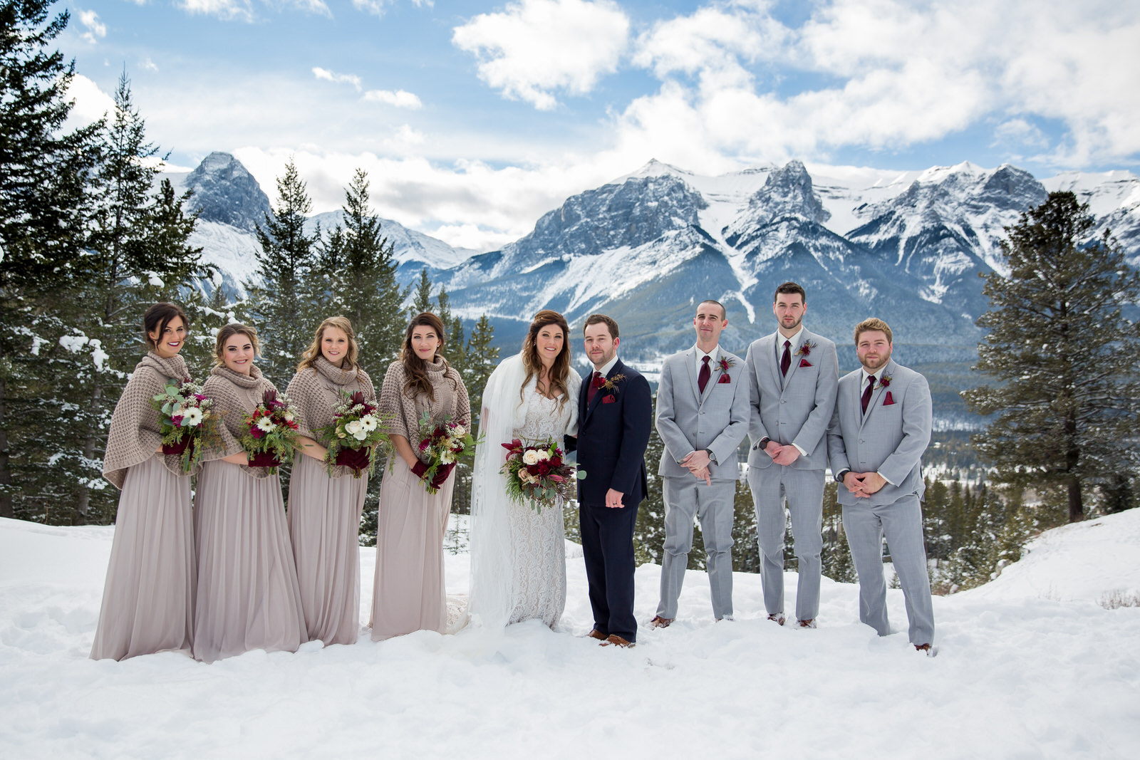 Winter wedding photos by gazebo at Silvertip Resort in Canmore, AB.