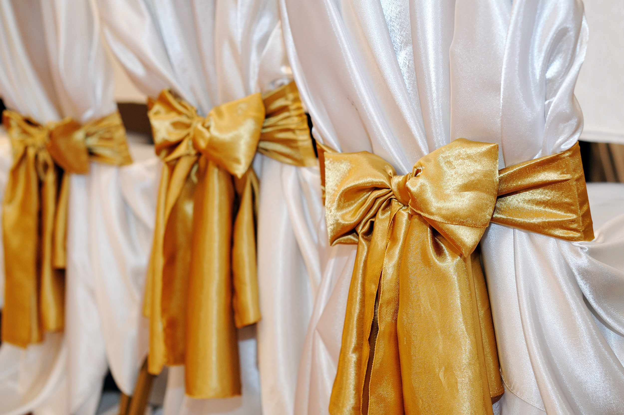 white satin tie back chair cover with gold satin sash