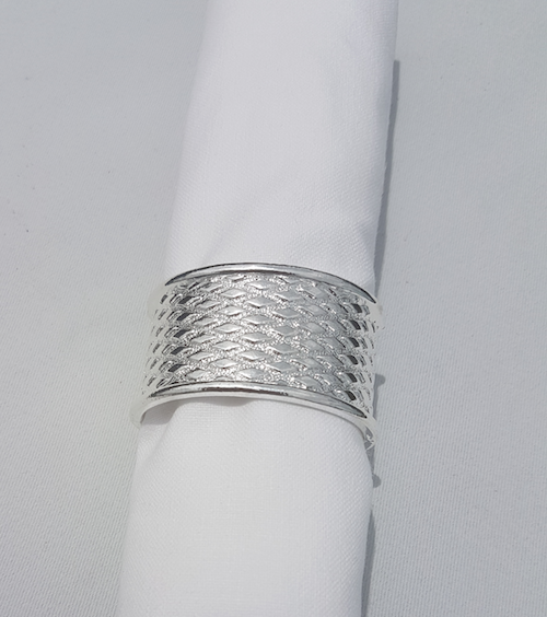 silver textured napkin ring with white rolled napkin