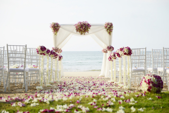 Beach Wedding with four post fabric arbour and pink florals