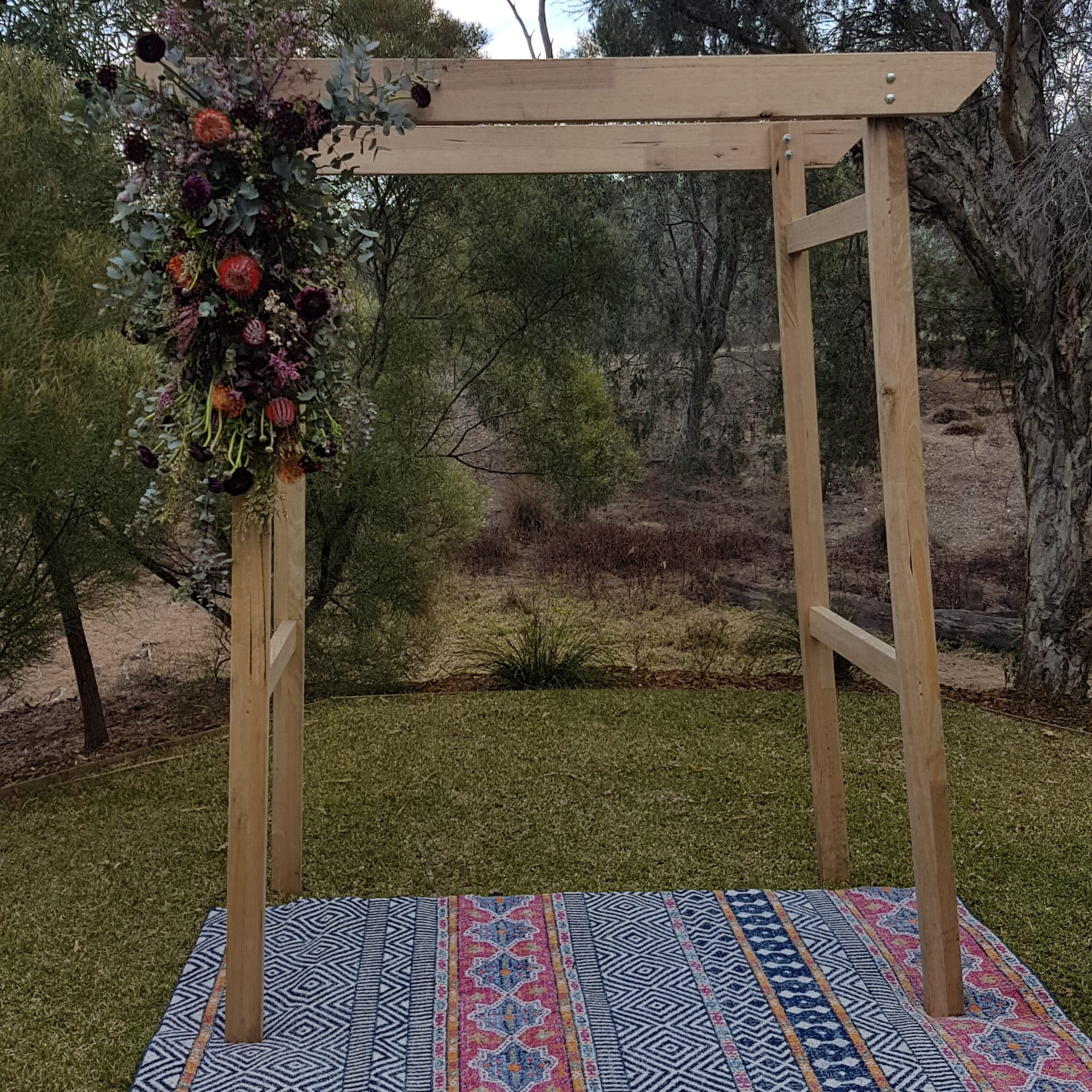 Boho ceremony arbour with boho rug and native floral styling