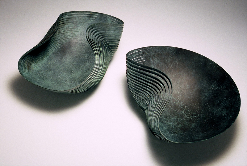 A pair of 'Dented Bowls' in verdigris copper