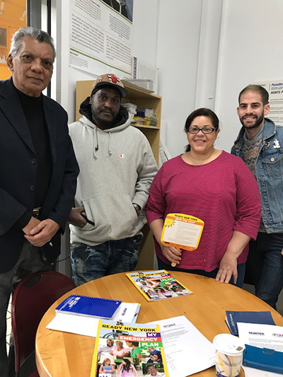 Fernando Ortiz (far right), climate preparedness and resiliency organizer at the Point Community Development Corporation and part of the Hunts Point Heat Project, teaches residents about individual preparedness at a public outreach event. Credit: Courtesy of Fernando Ortiz