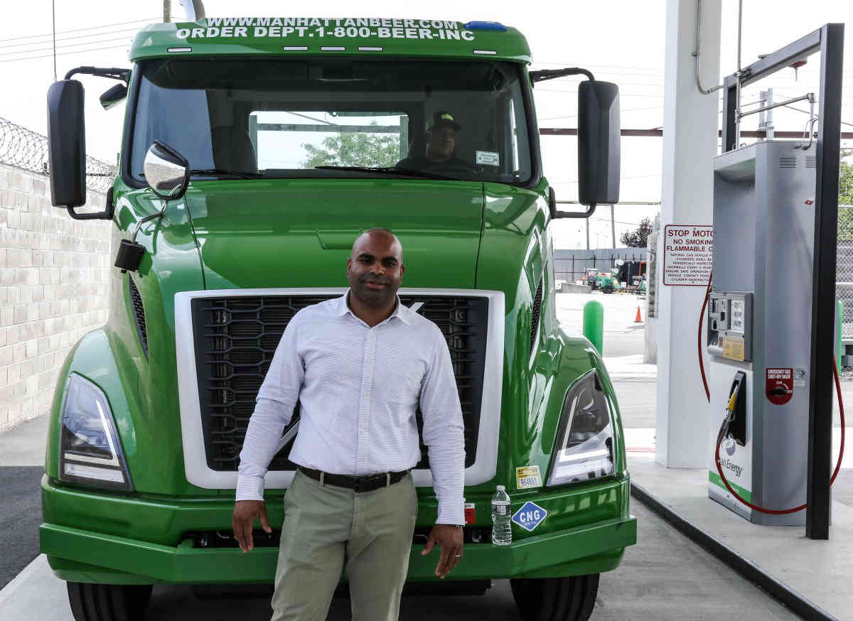 Juan Corcino, Manhattan Beer Distributors fleet director with his truck that runs on renewable clean energy.