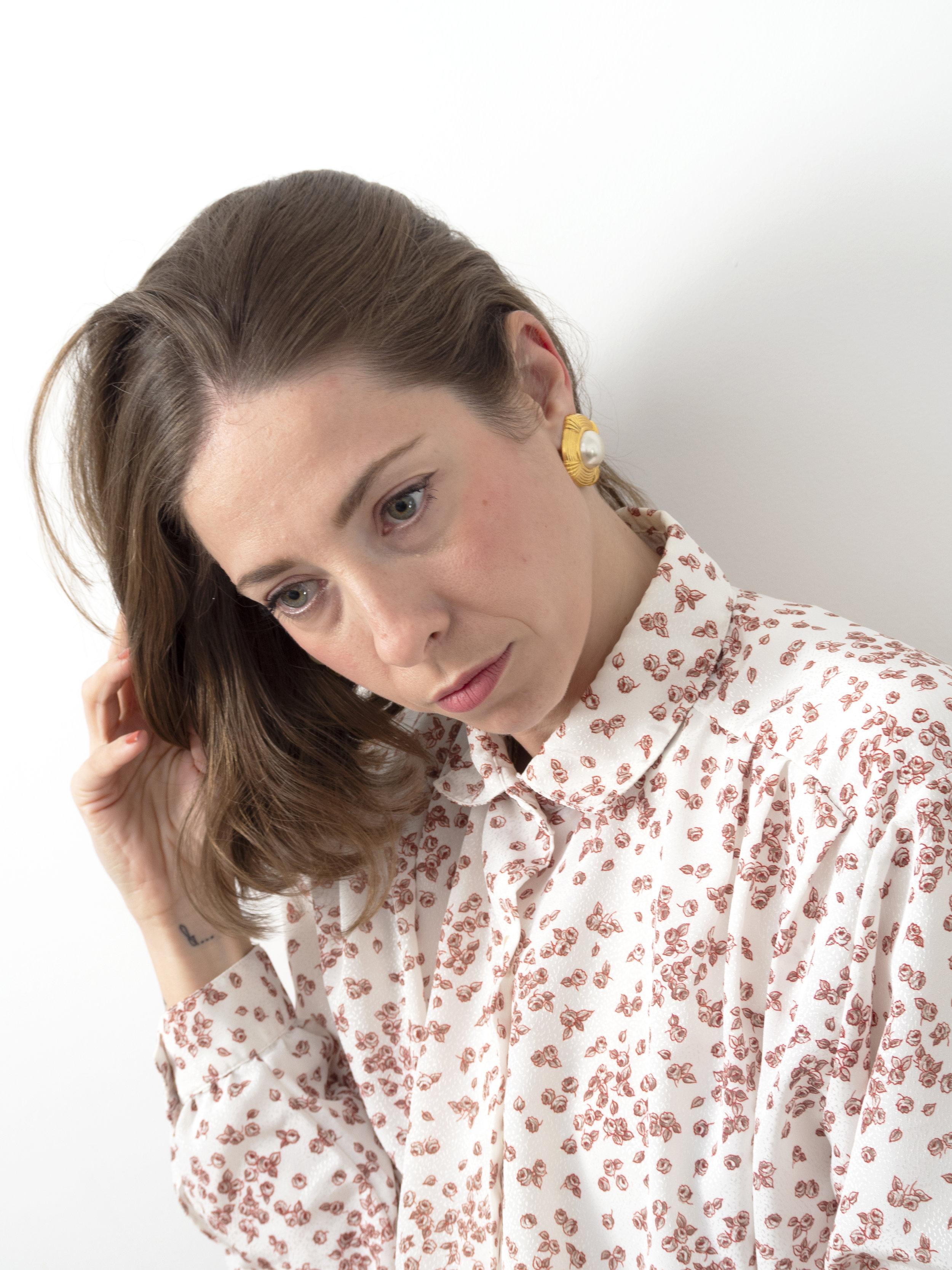 Flor es creadora y curadora de contenido visual, Imagen de marca, y Diseño.  En la foto, Flor viste camisa y pendientes de Neko vintage clothes.