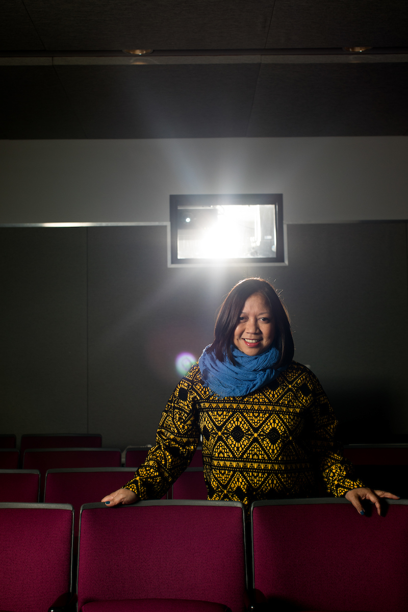 Ramona Diaz, standing in a movie theater under a lit projector