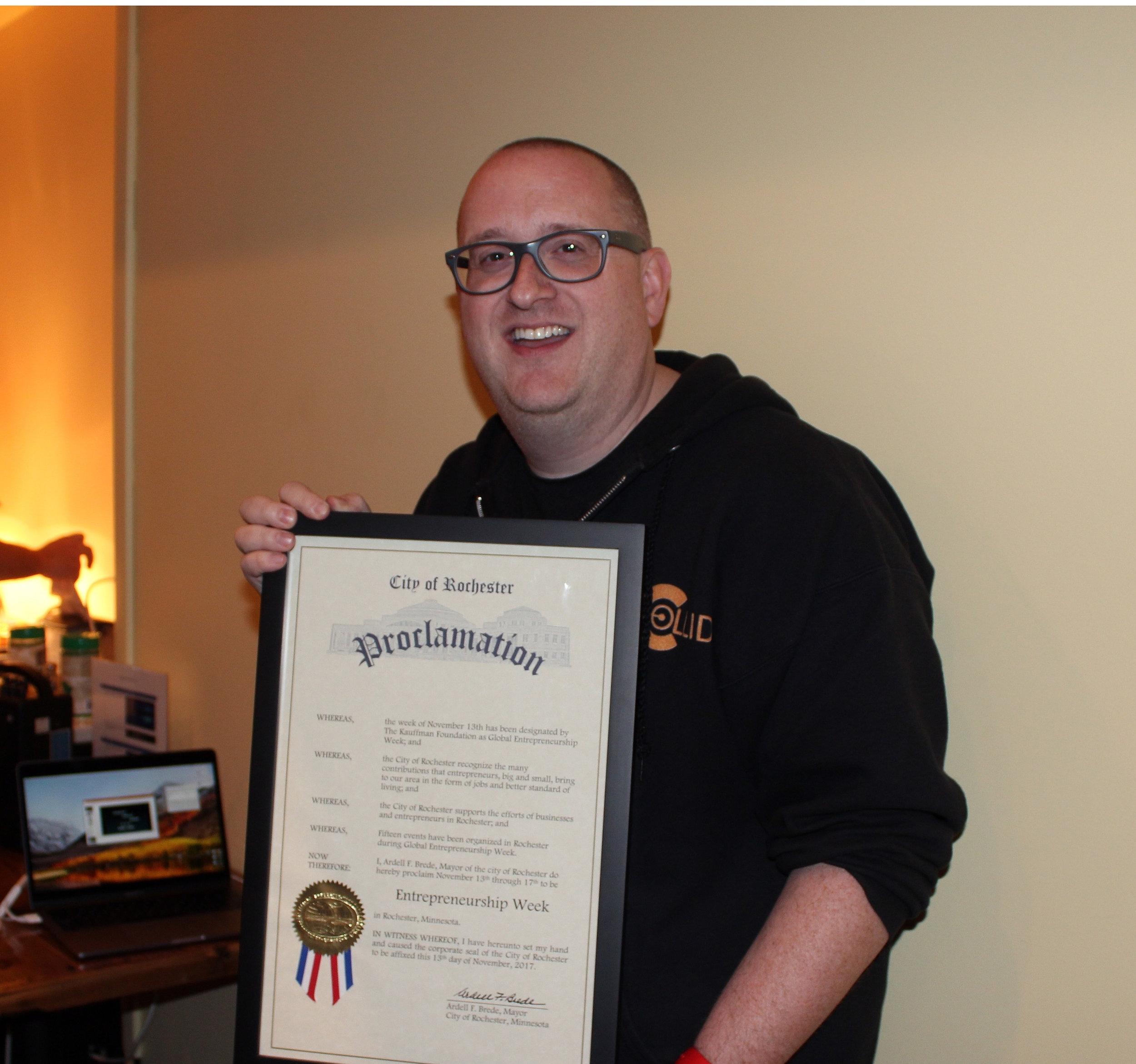 Rochester Global Entrepreneurship Week lead organizer Jamie Sundsbak holding the proclamation from Mayor Brede.