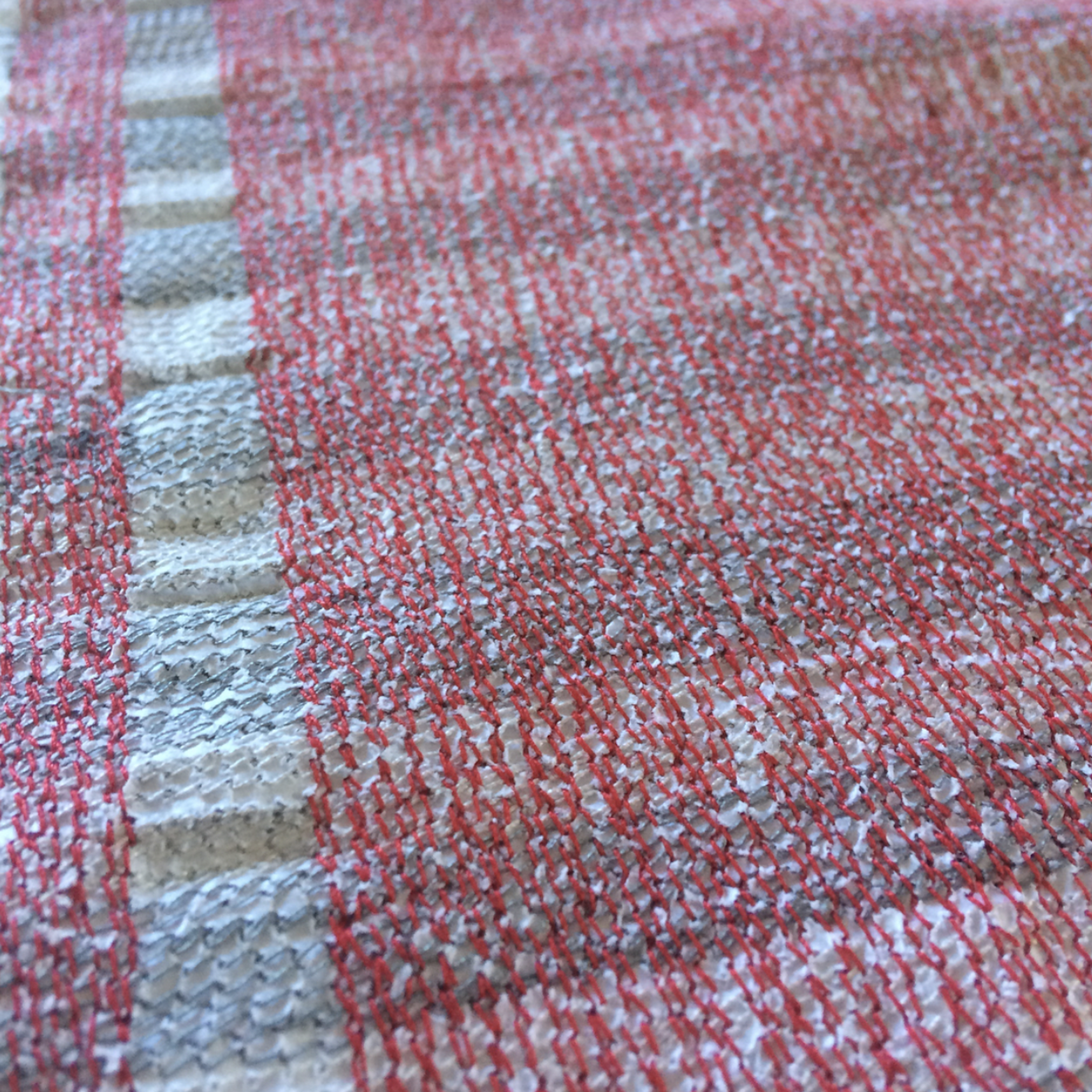 """This is a close-up of the piece I'm currently working on for exhibit in April this year. It involves stitching rows of thread into pages of the last edition of the """"Cambodia Daily"""" newspaper, which was deemed illegal by the government in September 2017 and is no longer in circulation. In pinning these pages together my intention is to create a wall hanging that serves to question the government's decision to disallow further publication of this newspaper."""