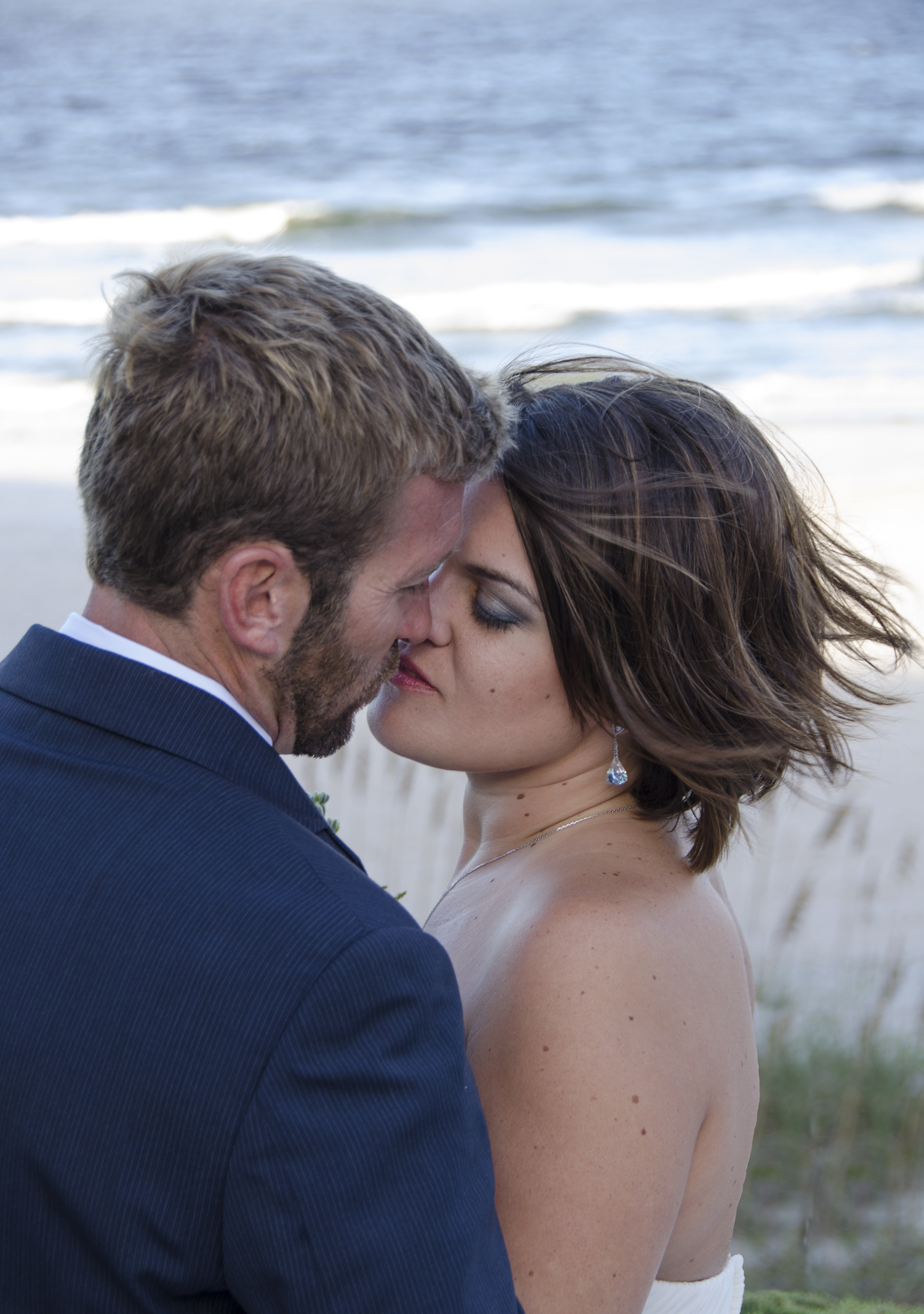 First kiss after the wedding ceremony, a tender moment by the beach