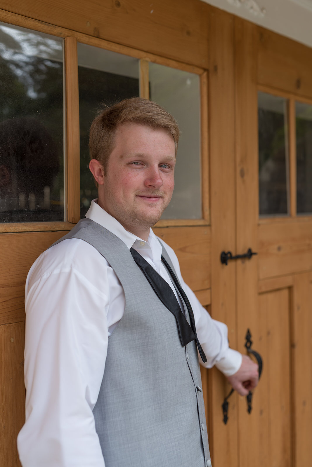 Groom by Large Wooden Doors at The Grande at Kennesaw