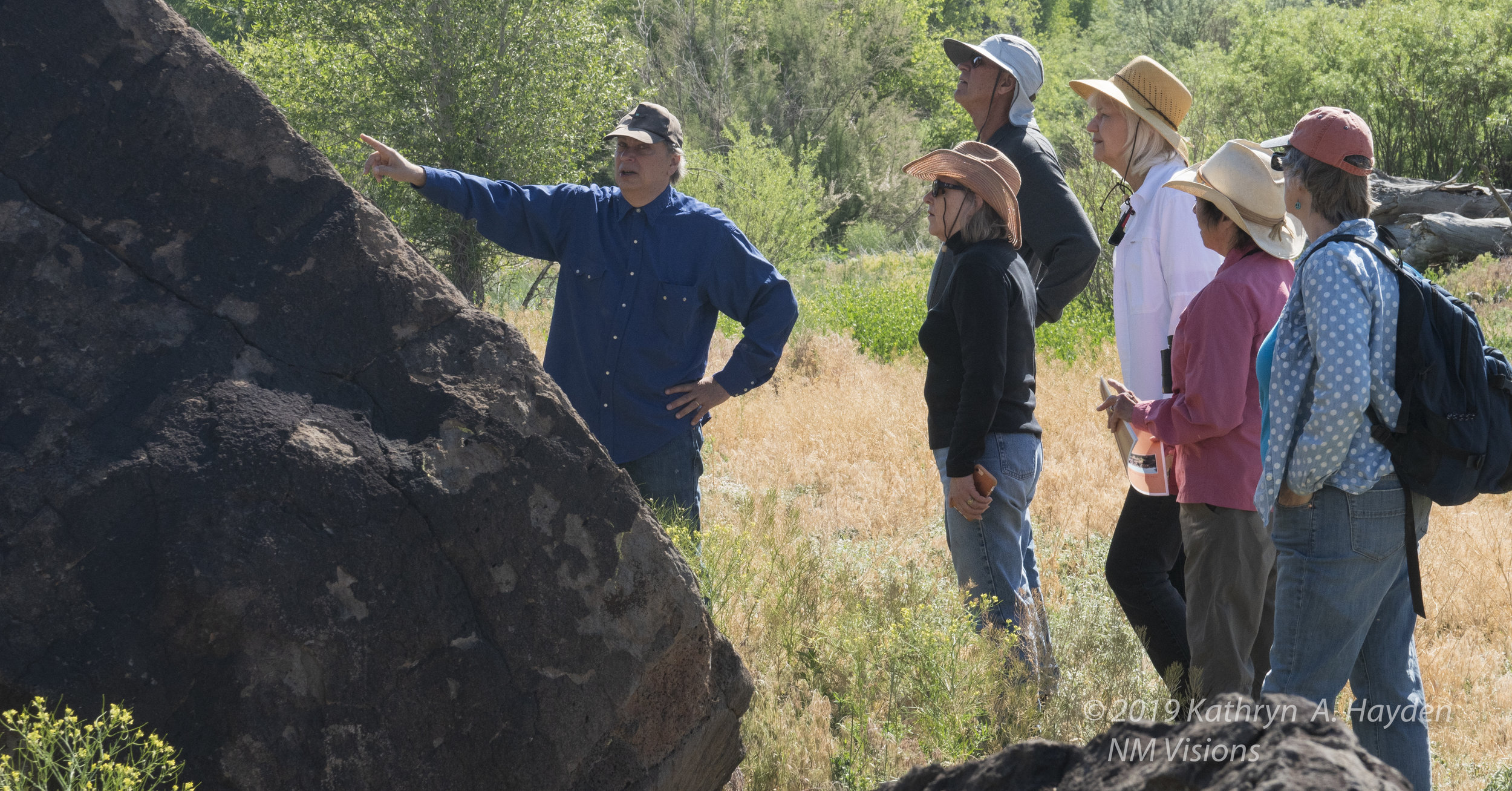 the group listens as Robert points out more petroglyphs and some of the theories about their origins and meanings.