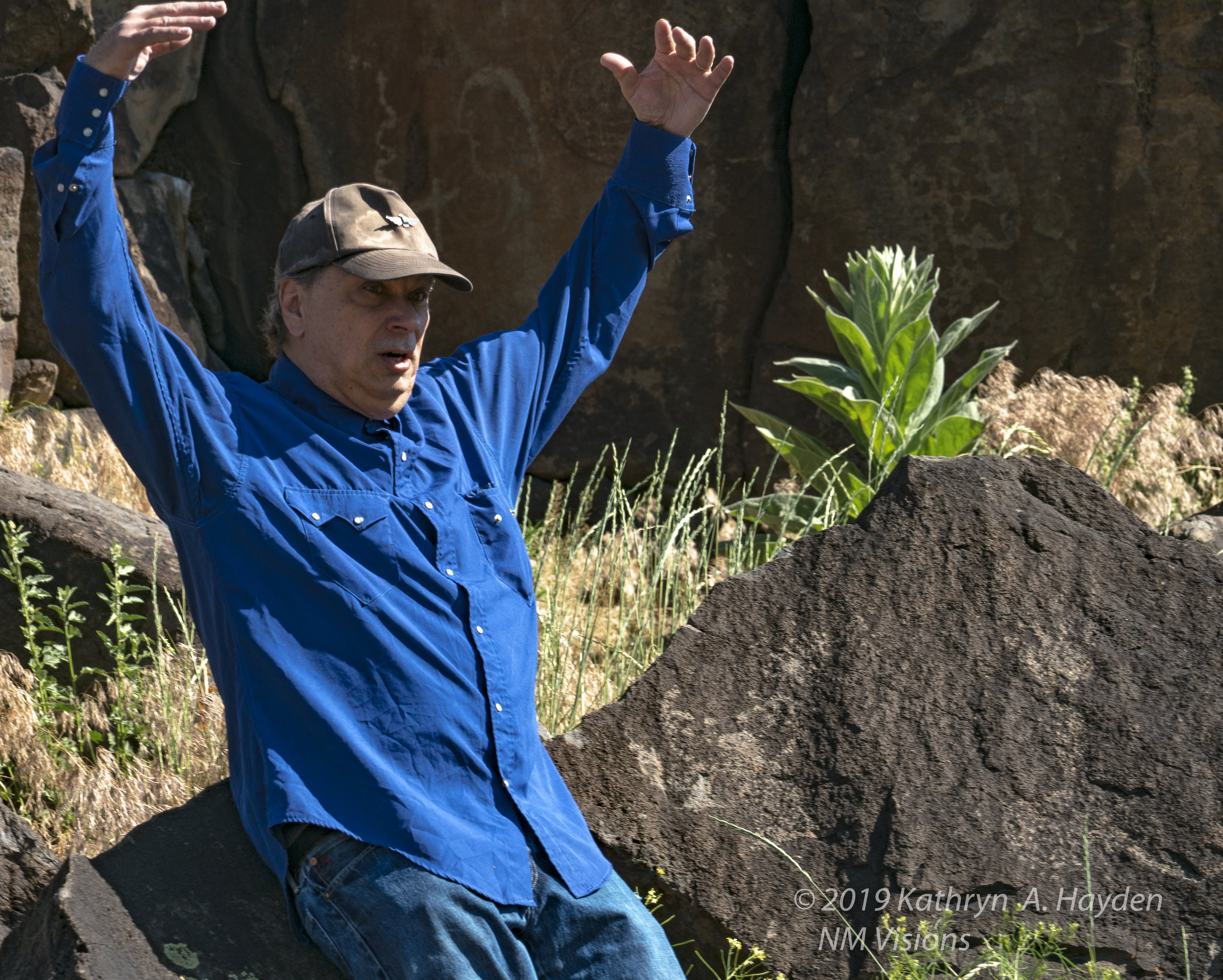 Robert demonstrates the view of the owl with wings spread that is on rock behind him