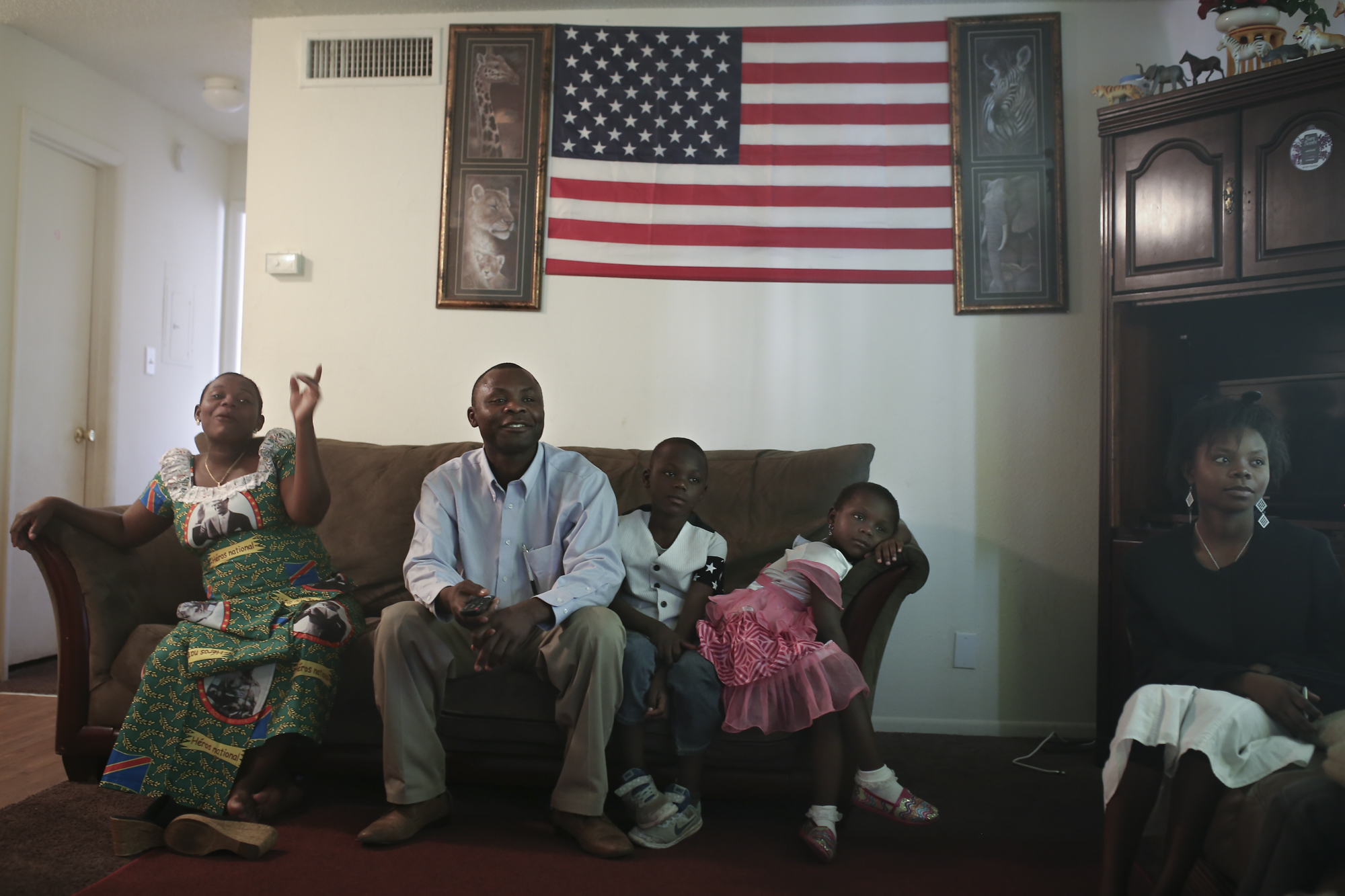 Sadiki Bertin (second to left) spends part of Mother's Day with his wife, Cecilia Kashindi Charlotte, 30 and children, Desire, 11, Mary, 6 and niece, Geannete Echa, 17, (from left) at a neighbor's home in Tampa, Fla. Their direction is focused on the TV, watching Youtube videos of a Congolese gathering in Buffalo, NY where many of their friends resettled.