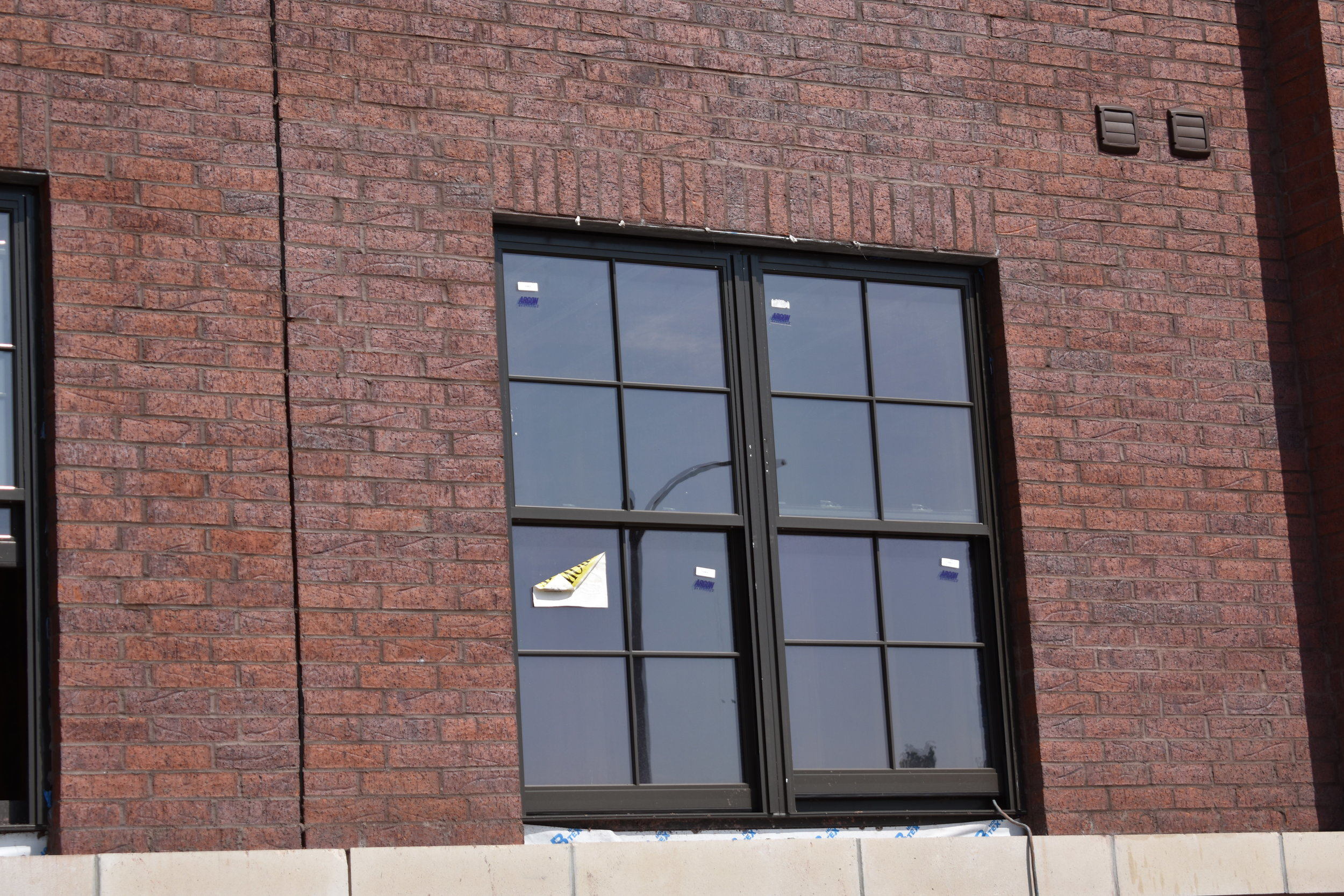 vertical brickwork above windows, texture/color of brick provides interest
