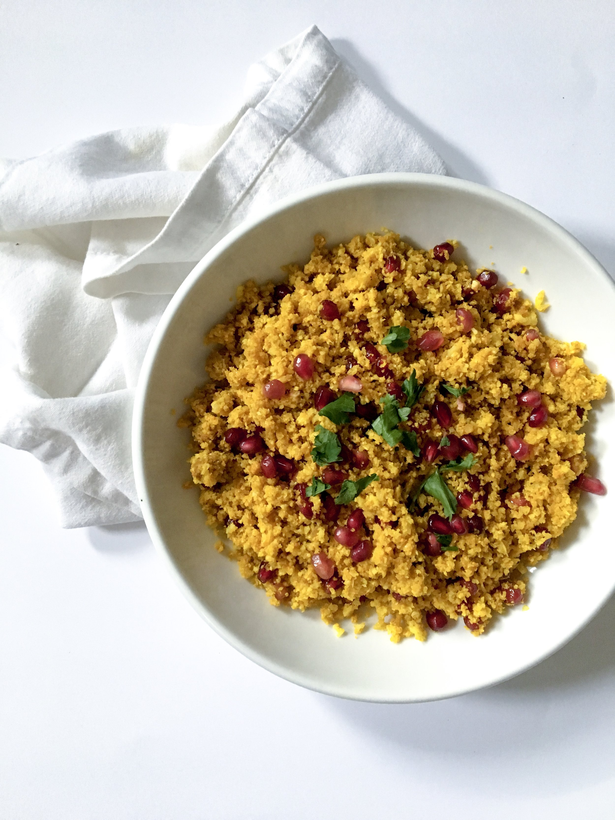 AIP Approved: Turmeric infused cauliflower rice mixed with pomegranate seeds and a hint of cinnamon and cloves.