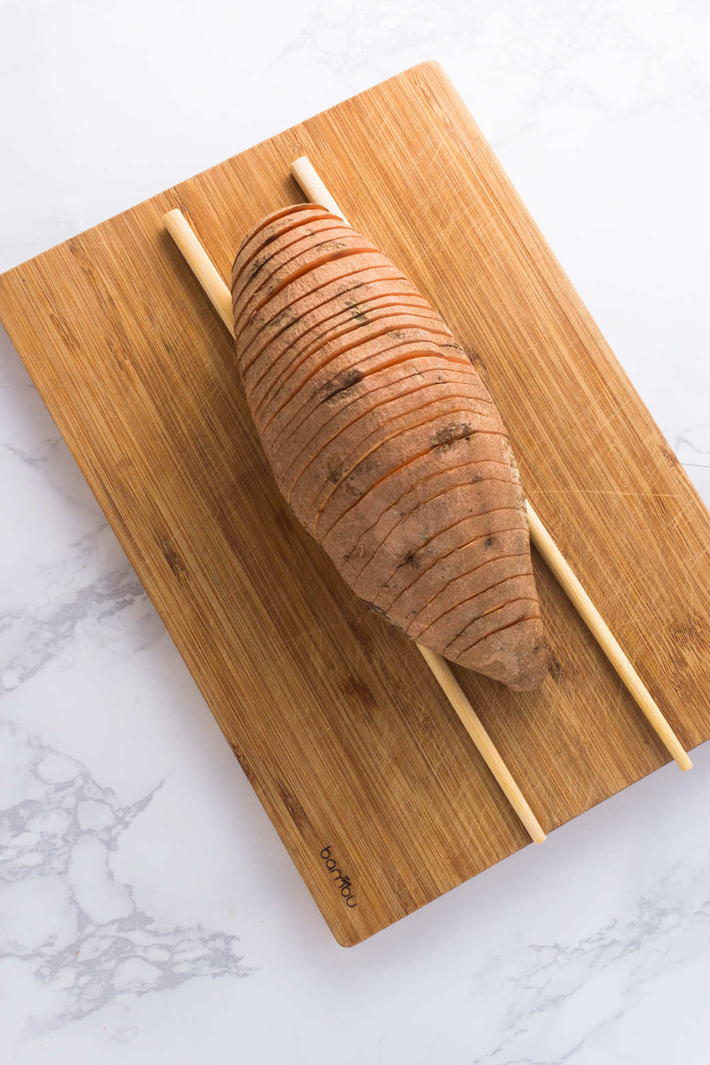 Using chopsticks on either side of the spud prevents you from cutting all of the way through.