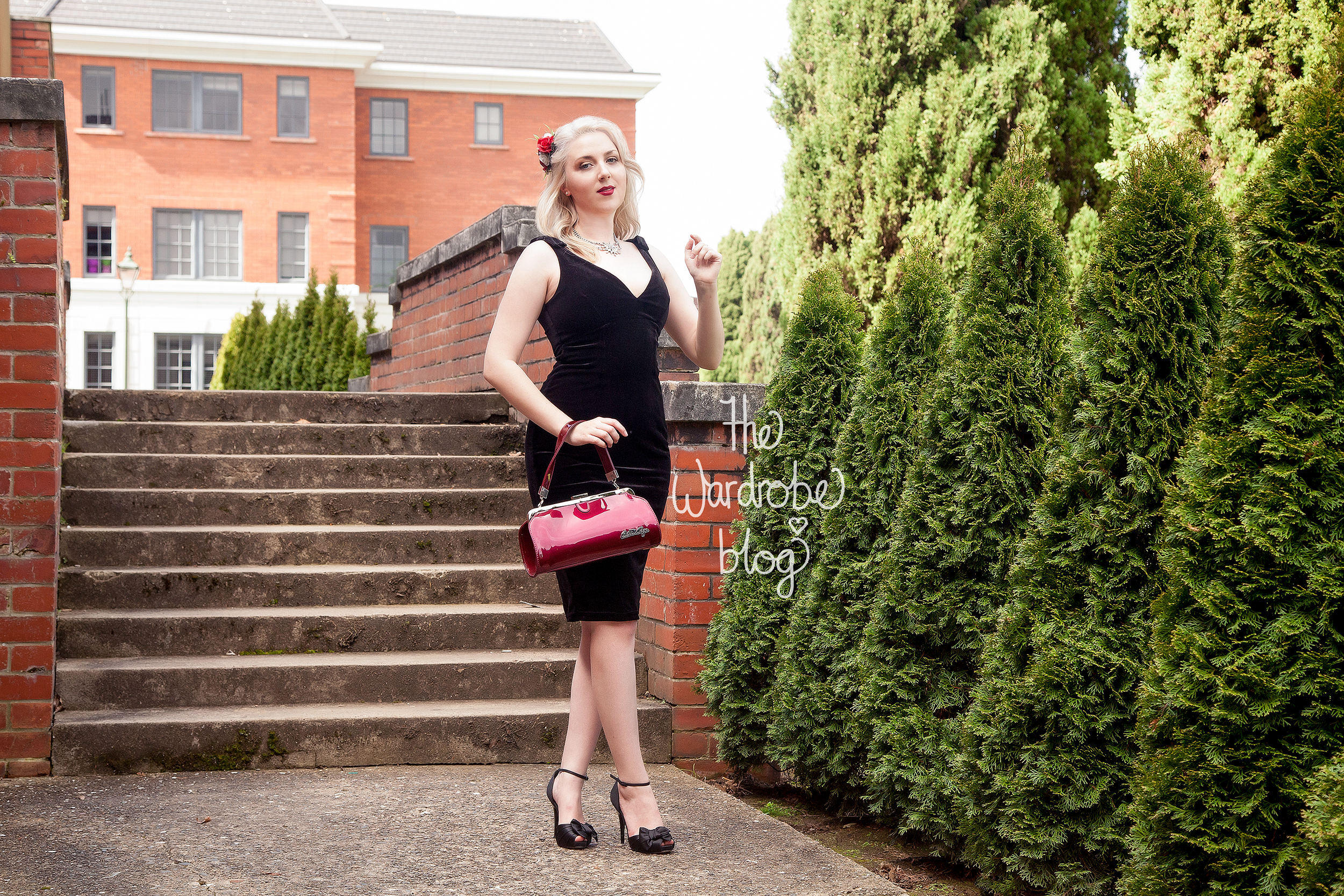 Laura Byrnes Gilda Dress in Black Velvet, Hair piece by Pop That Cassette, and Bettie Page Cover Girl Purse in Maroon by Sourpuss, both available at Rita Sue. Necklace is vintage, and shoes are from Novo shoes.