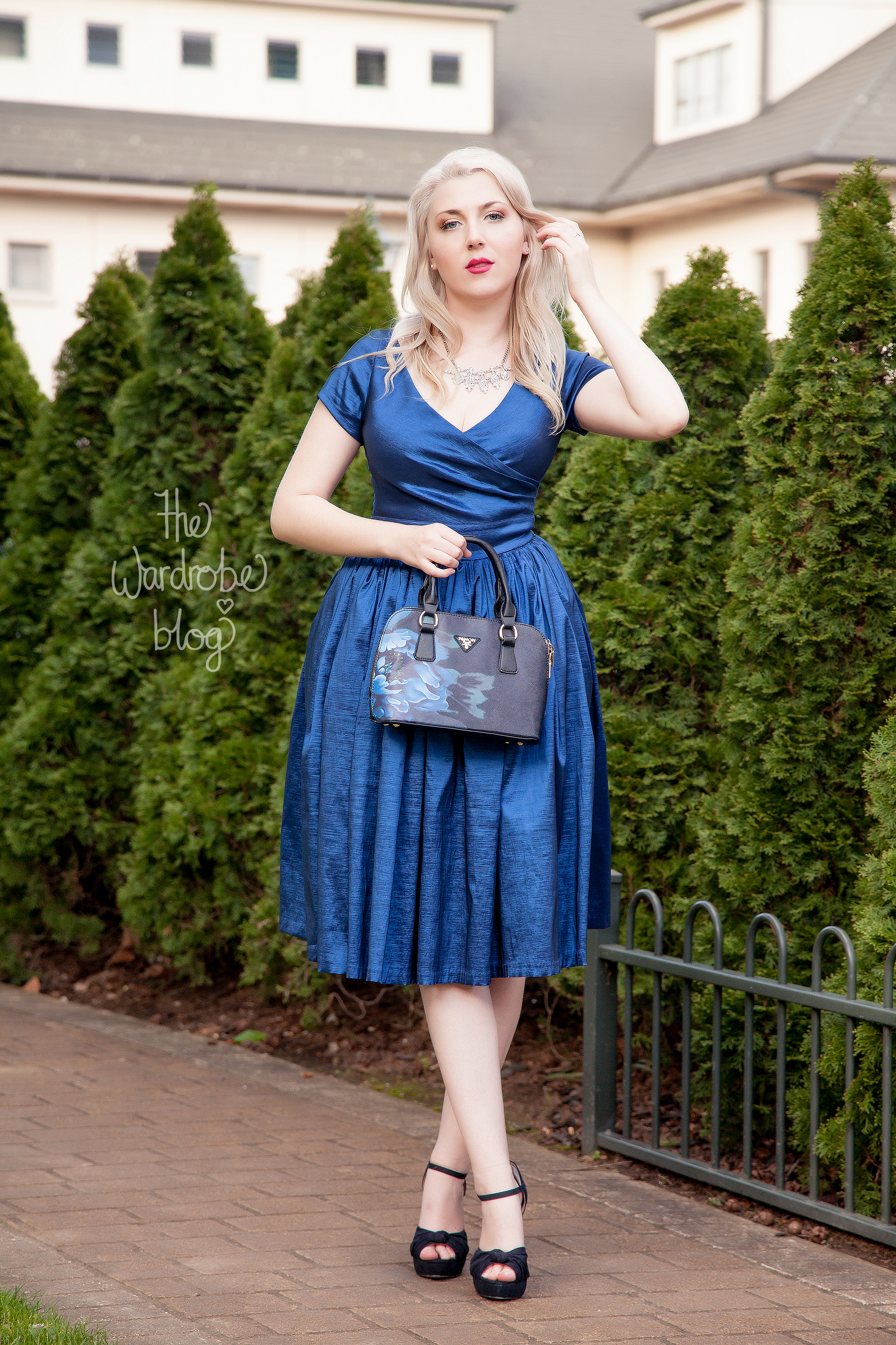 Ava Swing Dress in Dark Blue available at the Rita Sue Boutique, by Pinup Girl Clothing.Finon Milano Handbag with blue illustration from the Rita Sue Boutique. Necklace from Veronica B. Shoes from Novo Shoes.