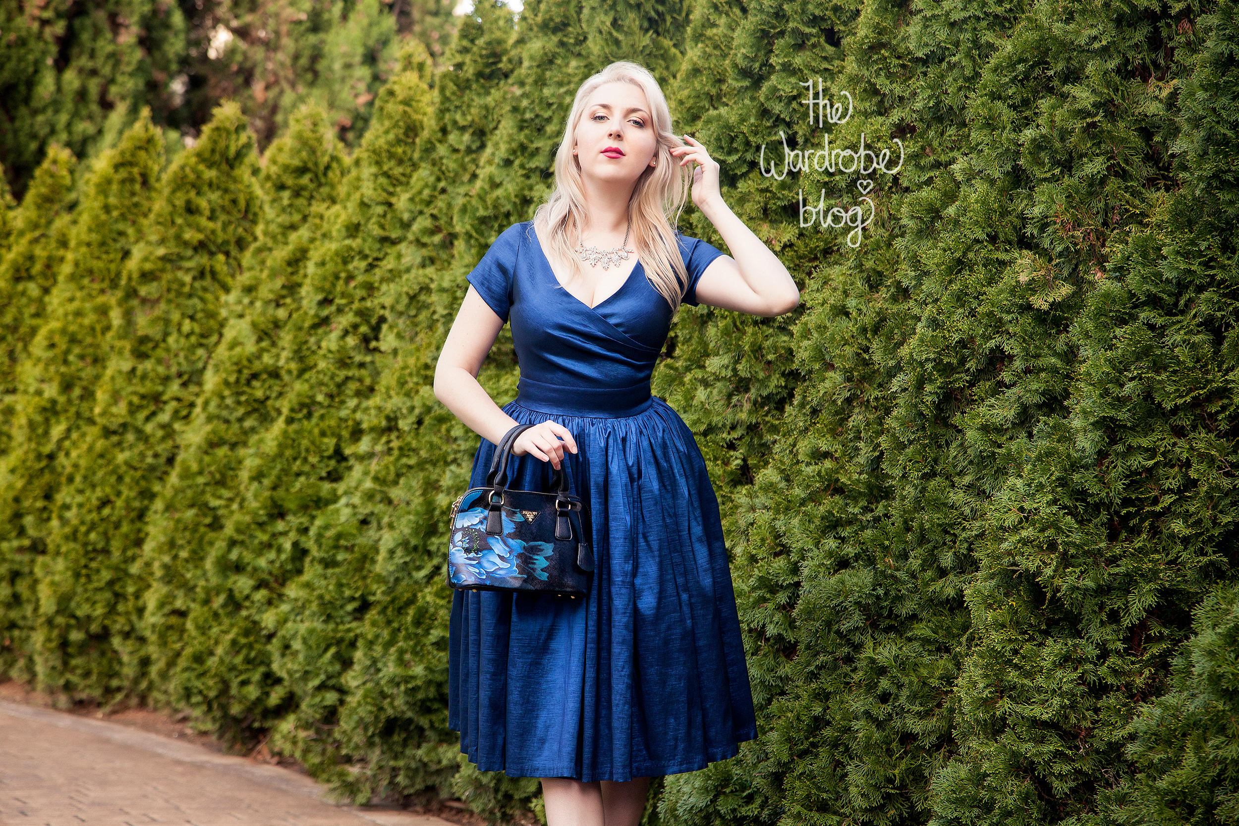 Ava Swing Dress in Dark Blue available at the Rita Sue Boutique, by Pinup Girl Clothing. Finon Milano Handbag with blue illustration from the Rita Sue Boutique. Necklace from Veronica B.